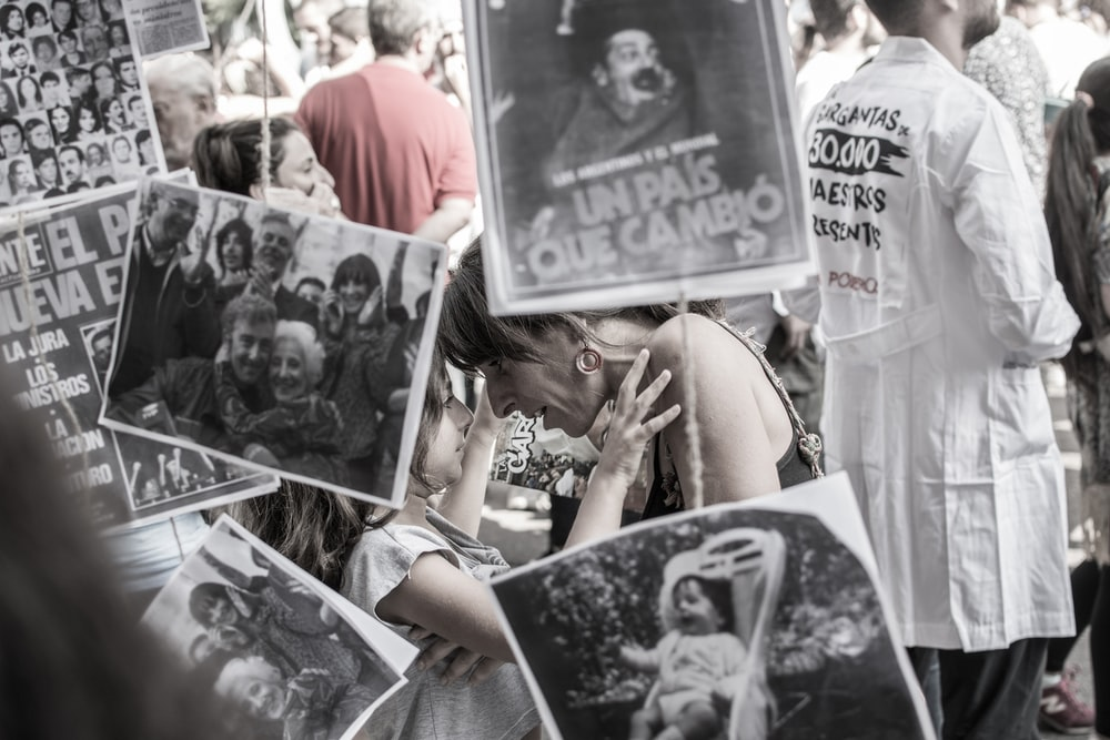 grayscale photography of woman and girl face to face while covering assorted photos