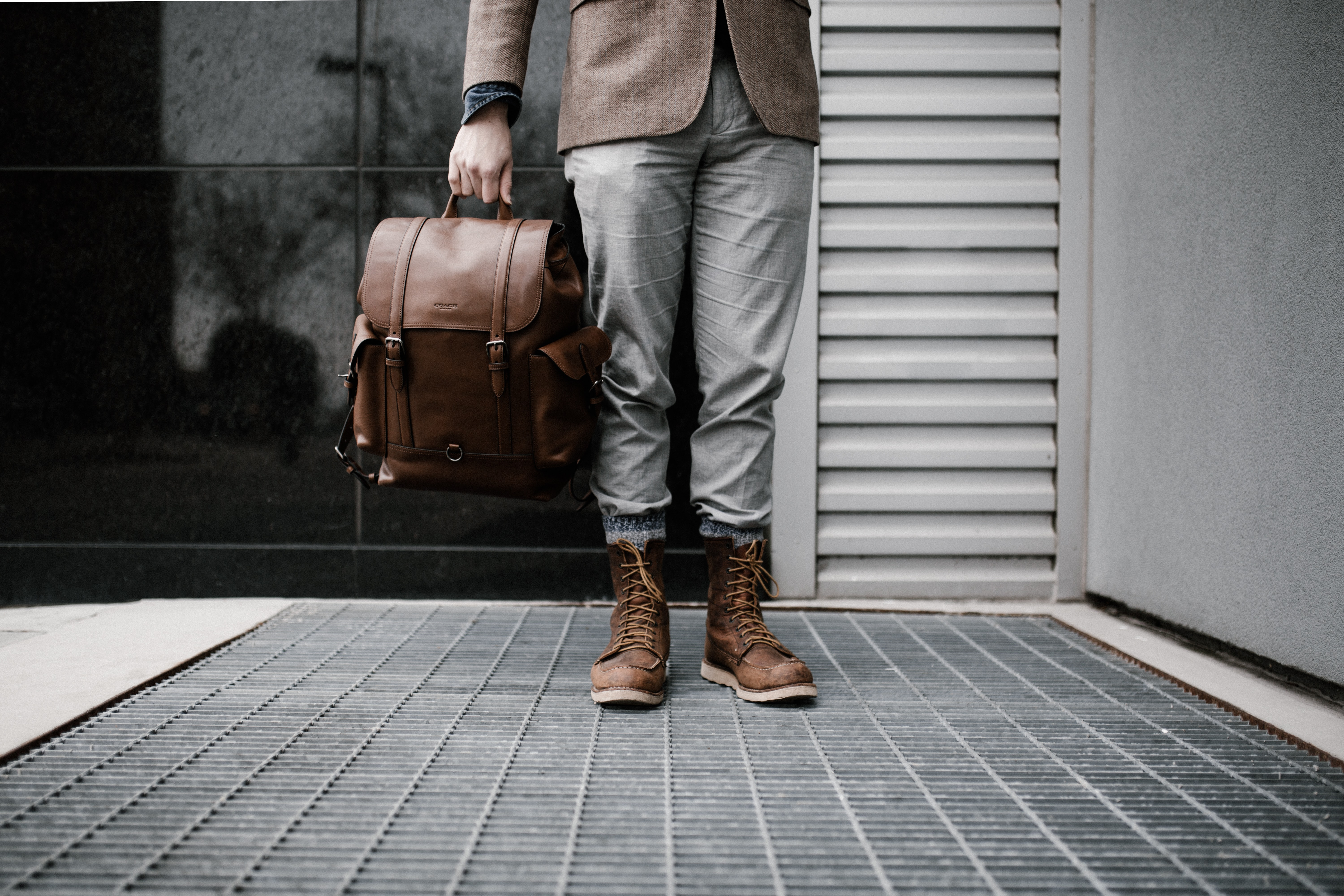 A low shot of a man in leather boots carrying a brown leather bag
