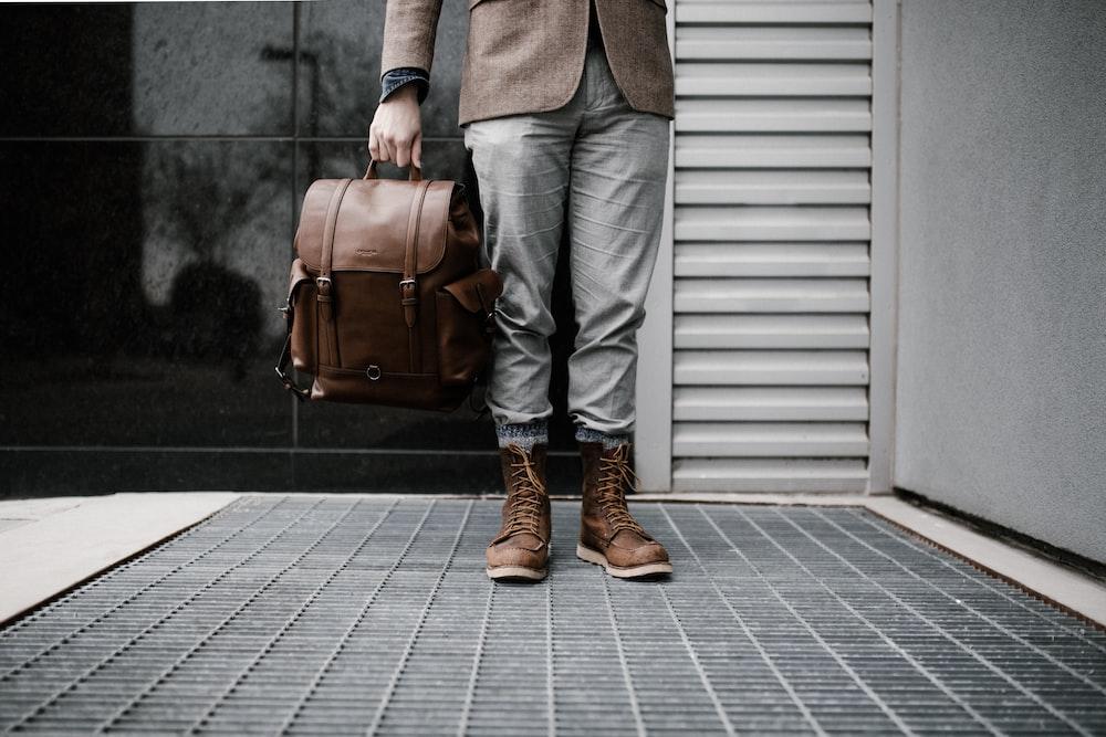 man wearing matching brown bag and shoes