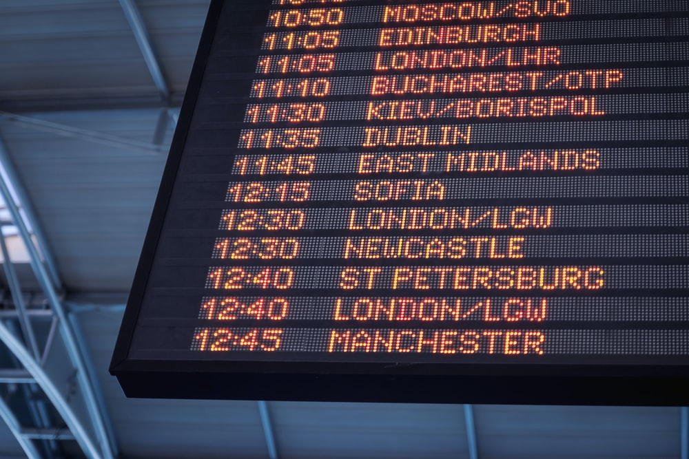 A low-angle shot of a departure board at an airport