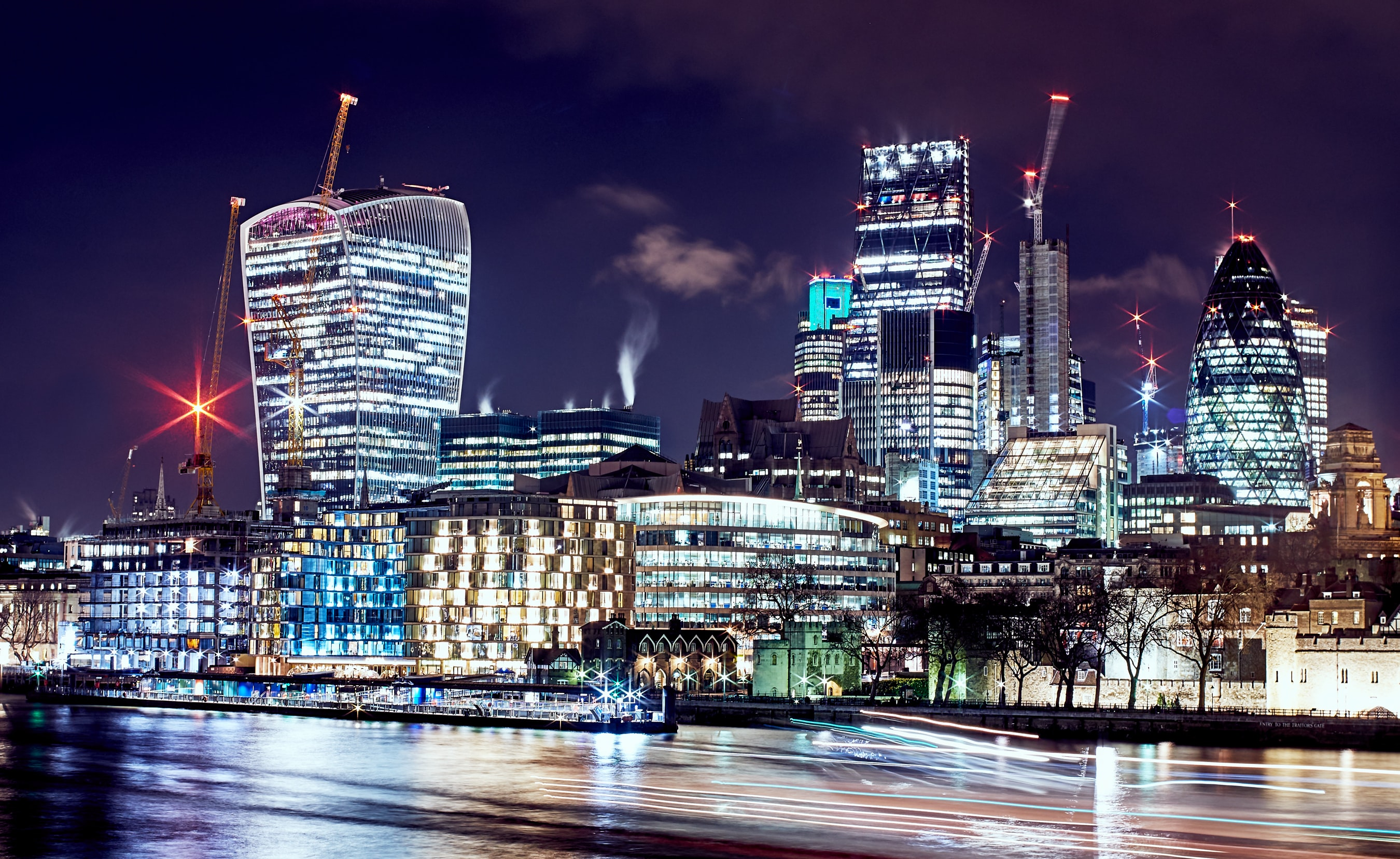 A cityscape background featuring well lit buildings and skyscrapers at night in London