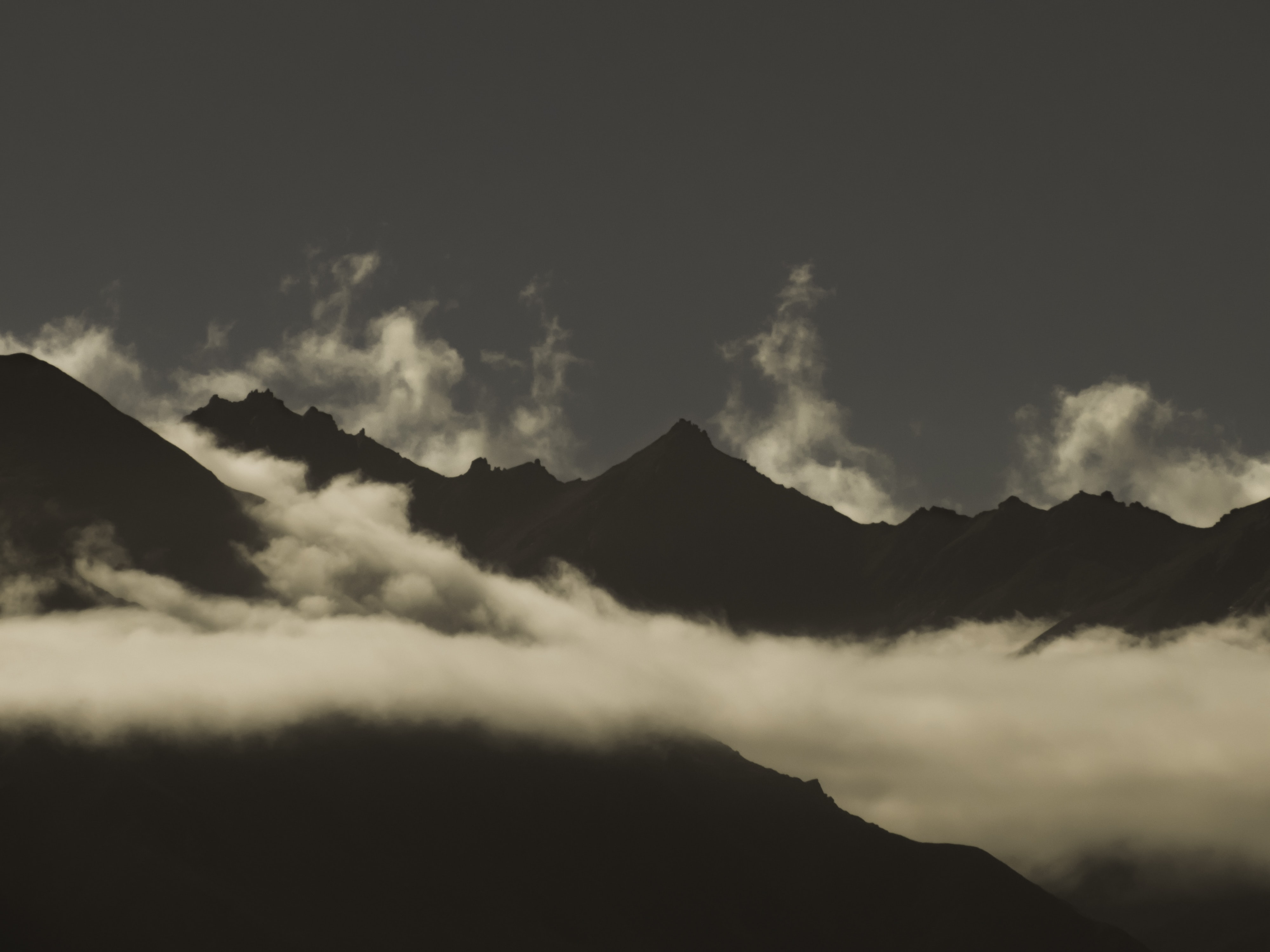 Silhouettes of sharp mountain peaks enveloped in white clouds near Lake Wanaka