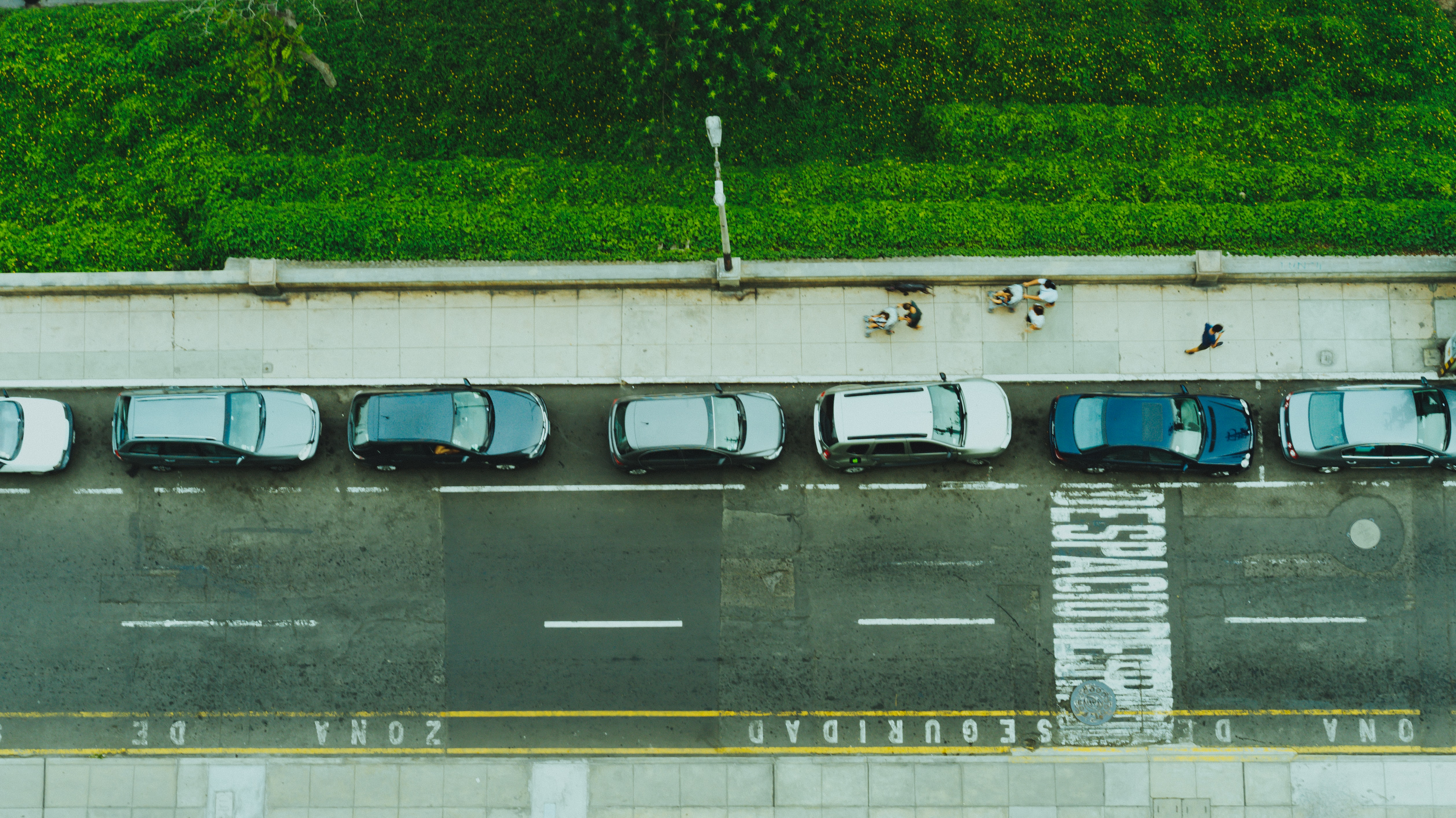 Drone shot of a row of cars parked by the curb.