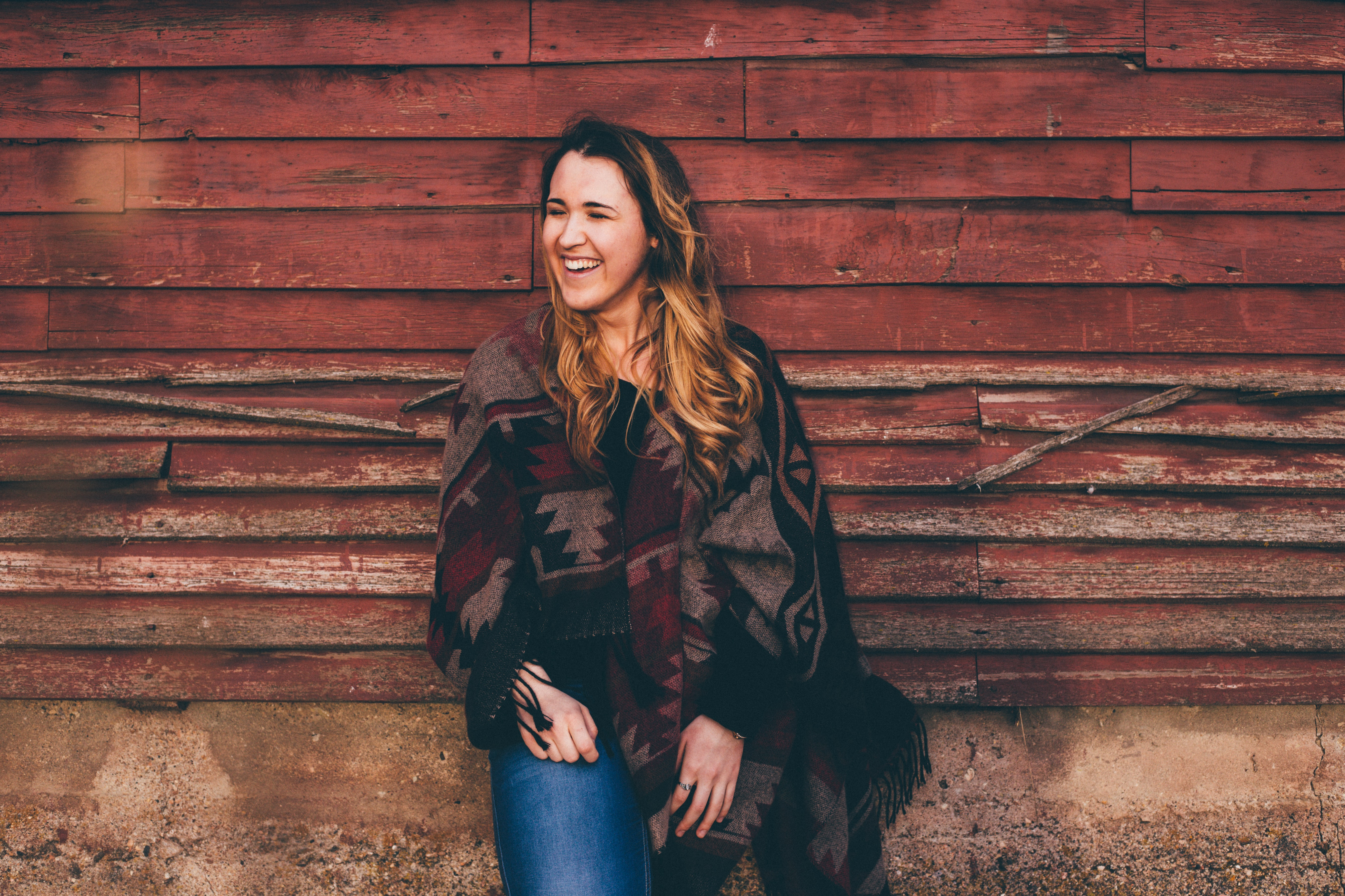 A happy woman standing against a red wall.
