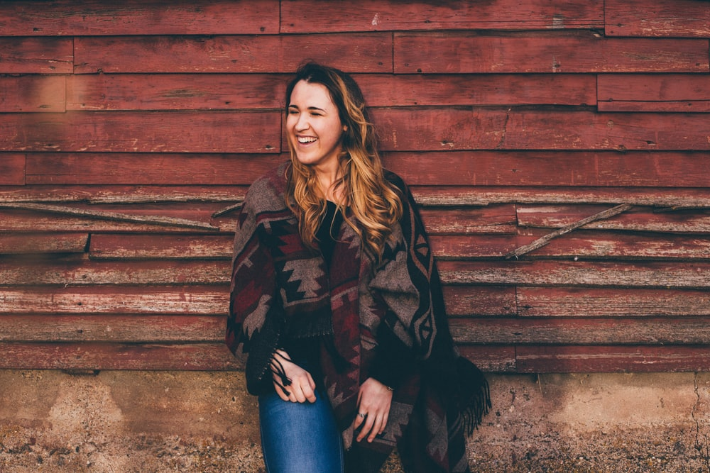 smiling woman wearing brown and black poncho leaning on wall
