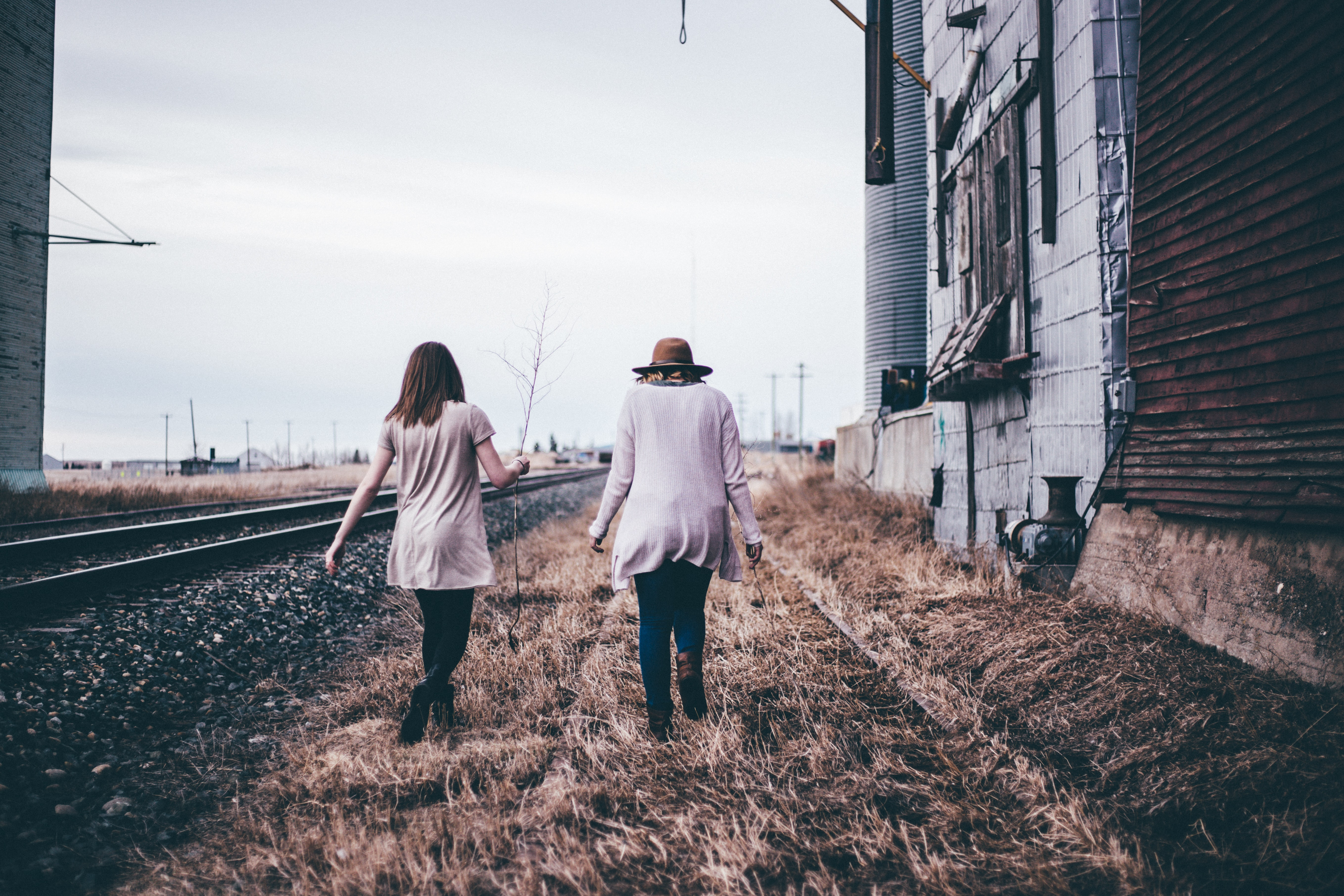 Two friends walk by abandoned railroad tracks in fall