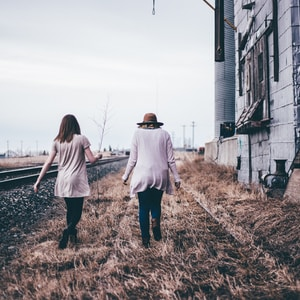 photo of two persons walking along railway
