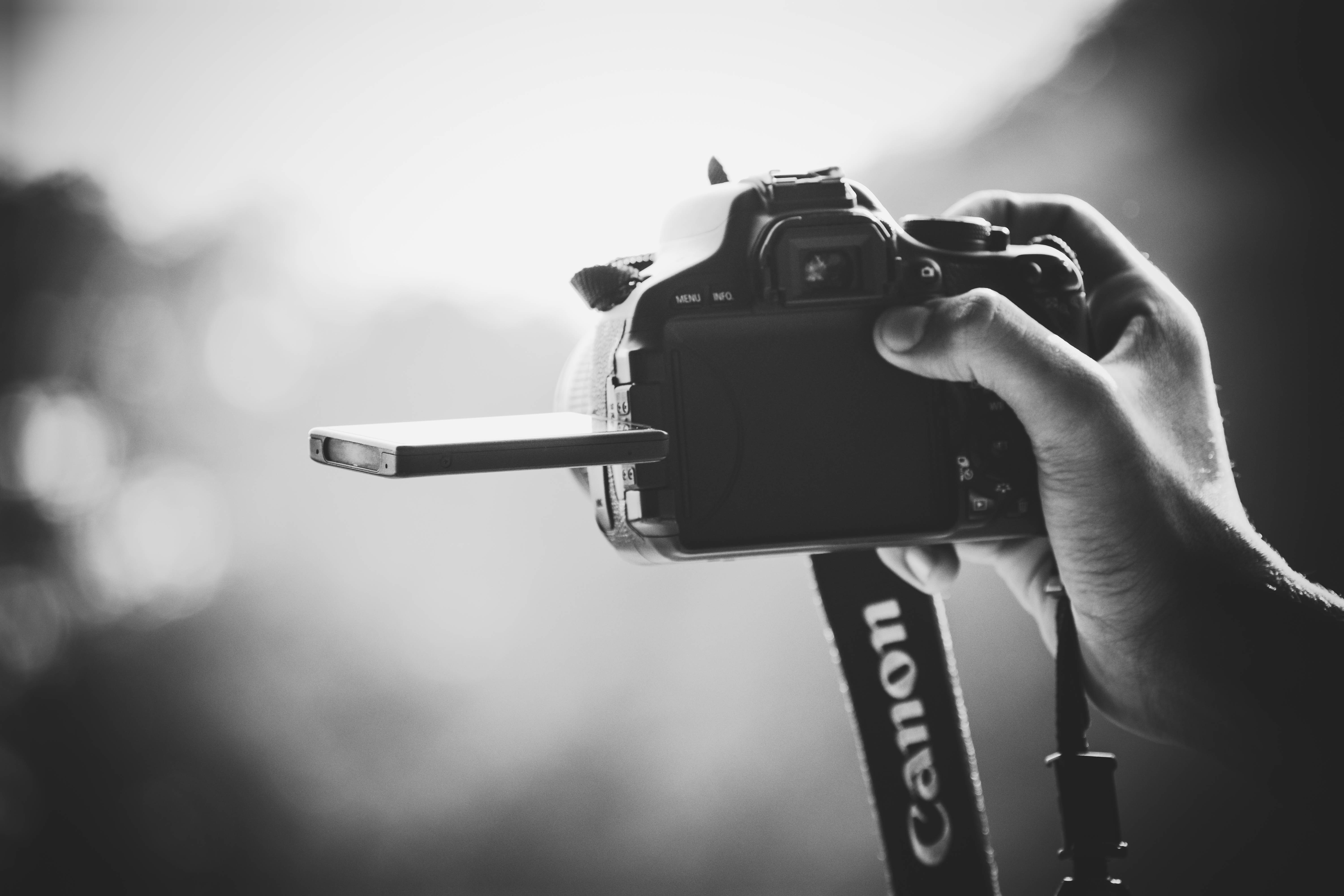 A black-and-white shot of a person holding a Canon camera