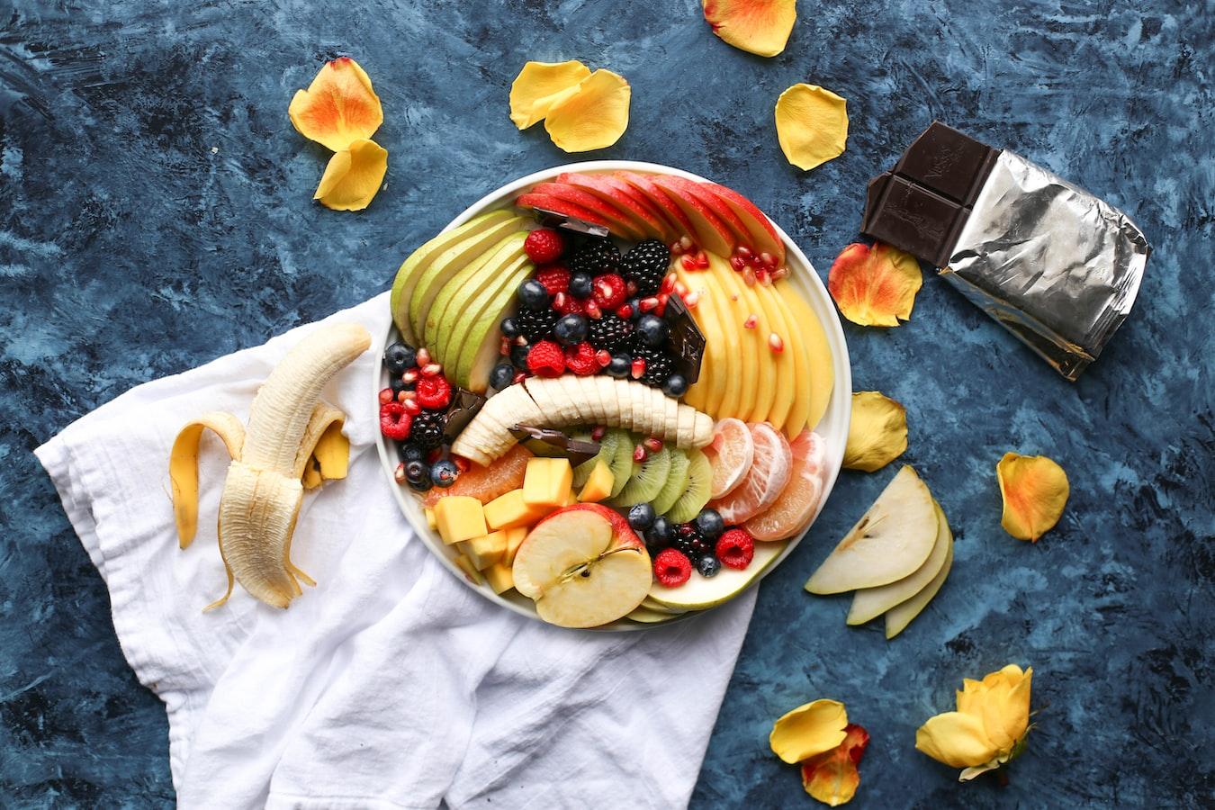 aufgeschnittenes Obst in einer großen Schale auf einem Tuch vor schieferfarbenem Hintergrund neben einer angebrochenen Tafel Schokolade und Blütenblättern