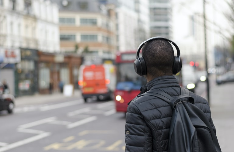 A man wearing headphones facing away from the camera toward a street.