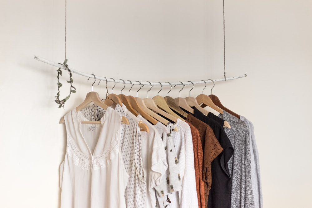 assorted clothes in wooden hangers