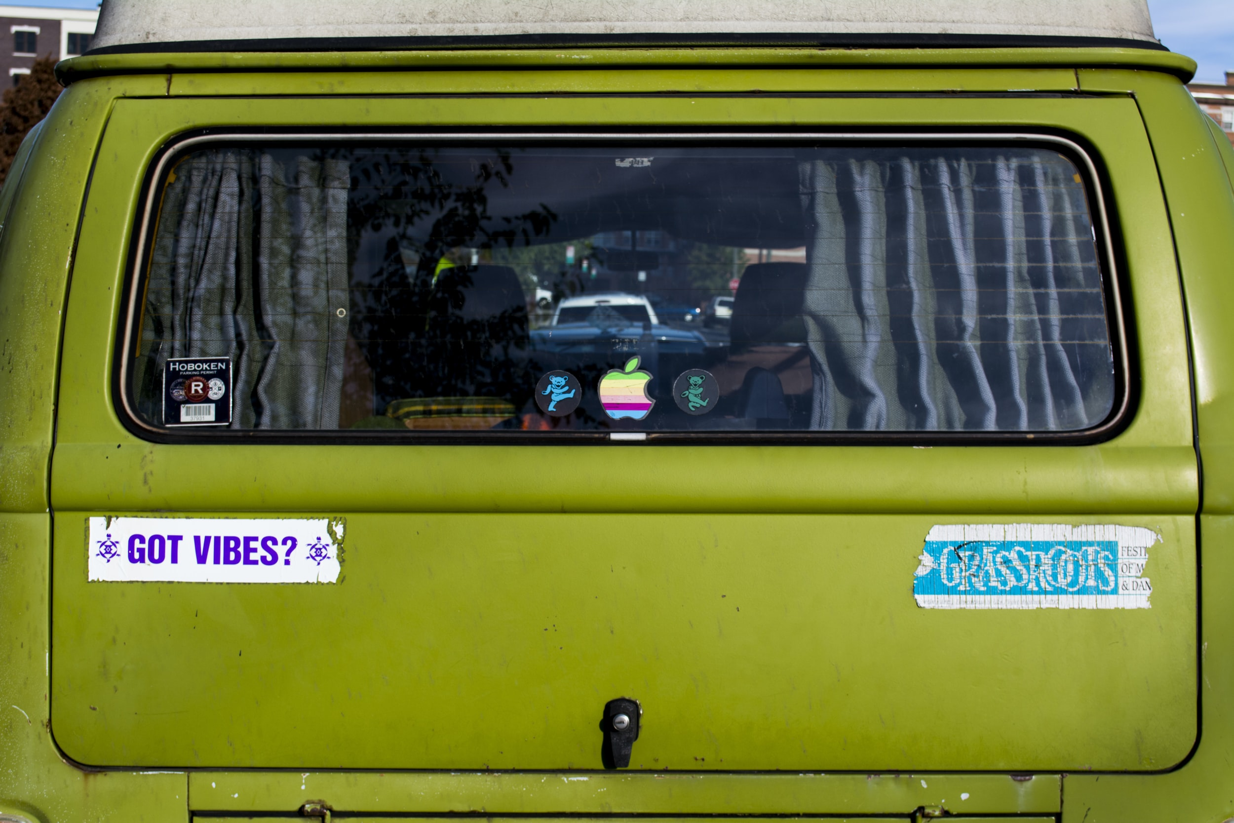 Colorful stickers on the rear window of a green Volkswagen van