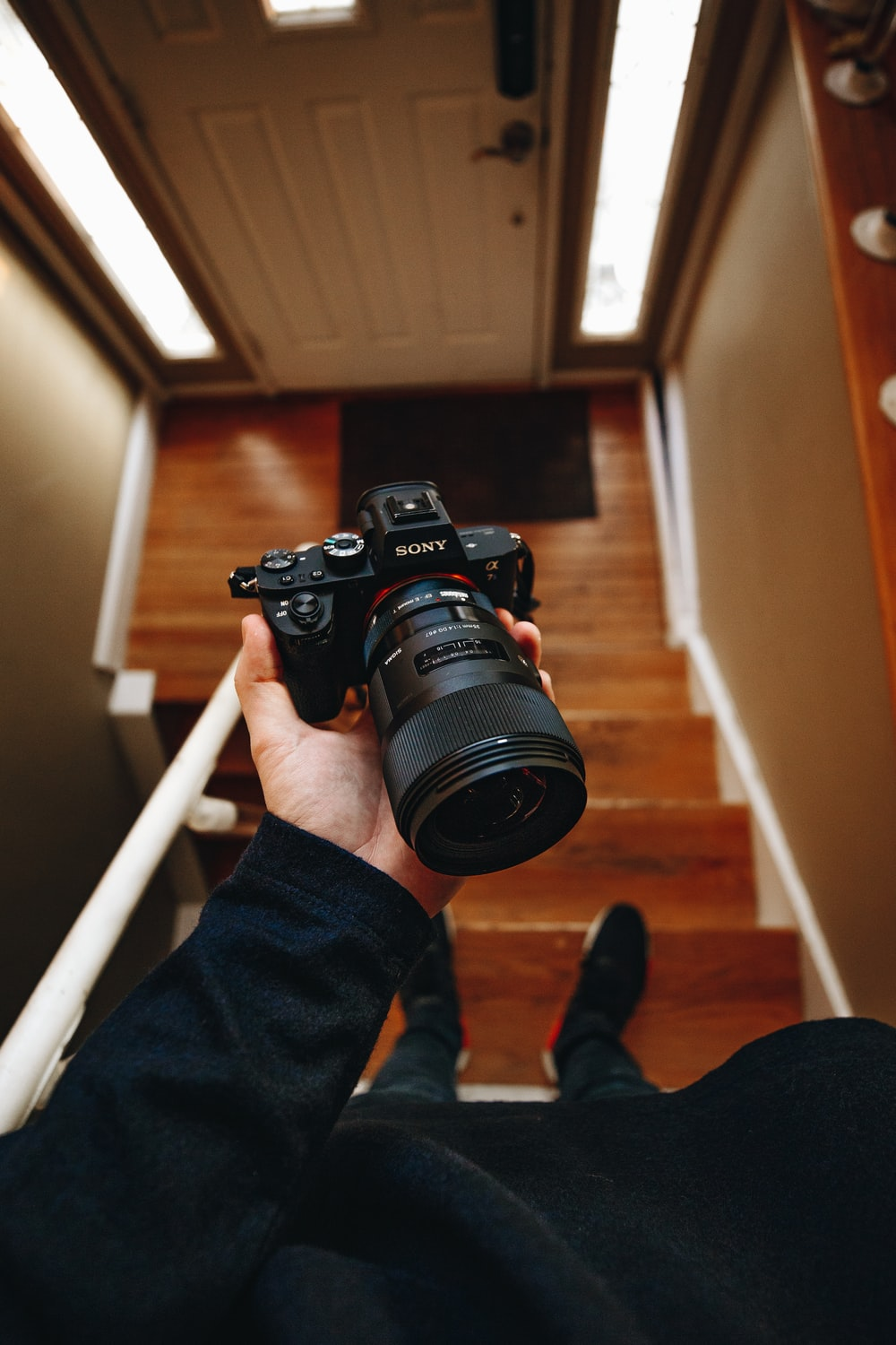 person holding black Sony DSLR camera on stair