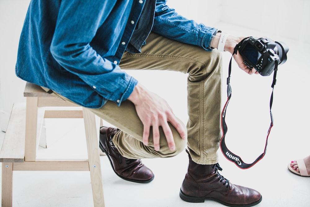 man holding DSLR camera while sitting on stool