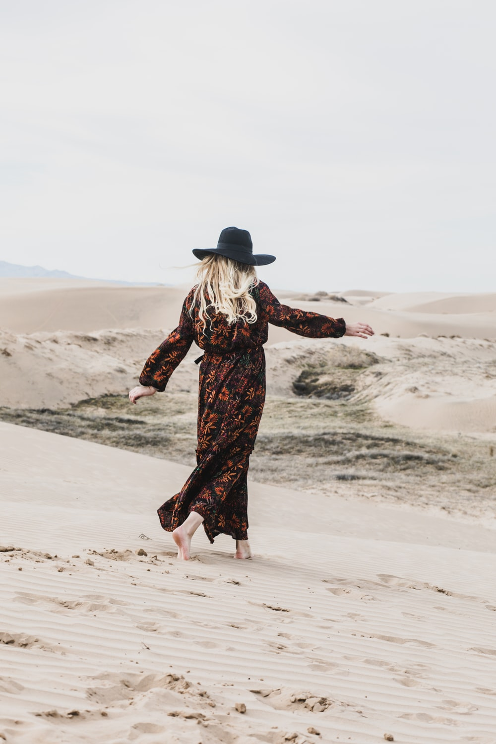 photo of person wearing brown and orange floral maxi dress walking barefooted along deserted land