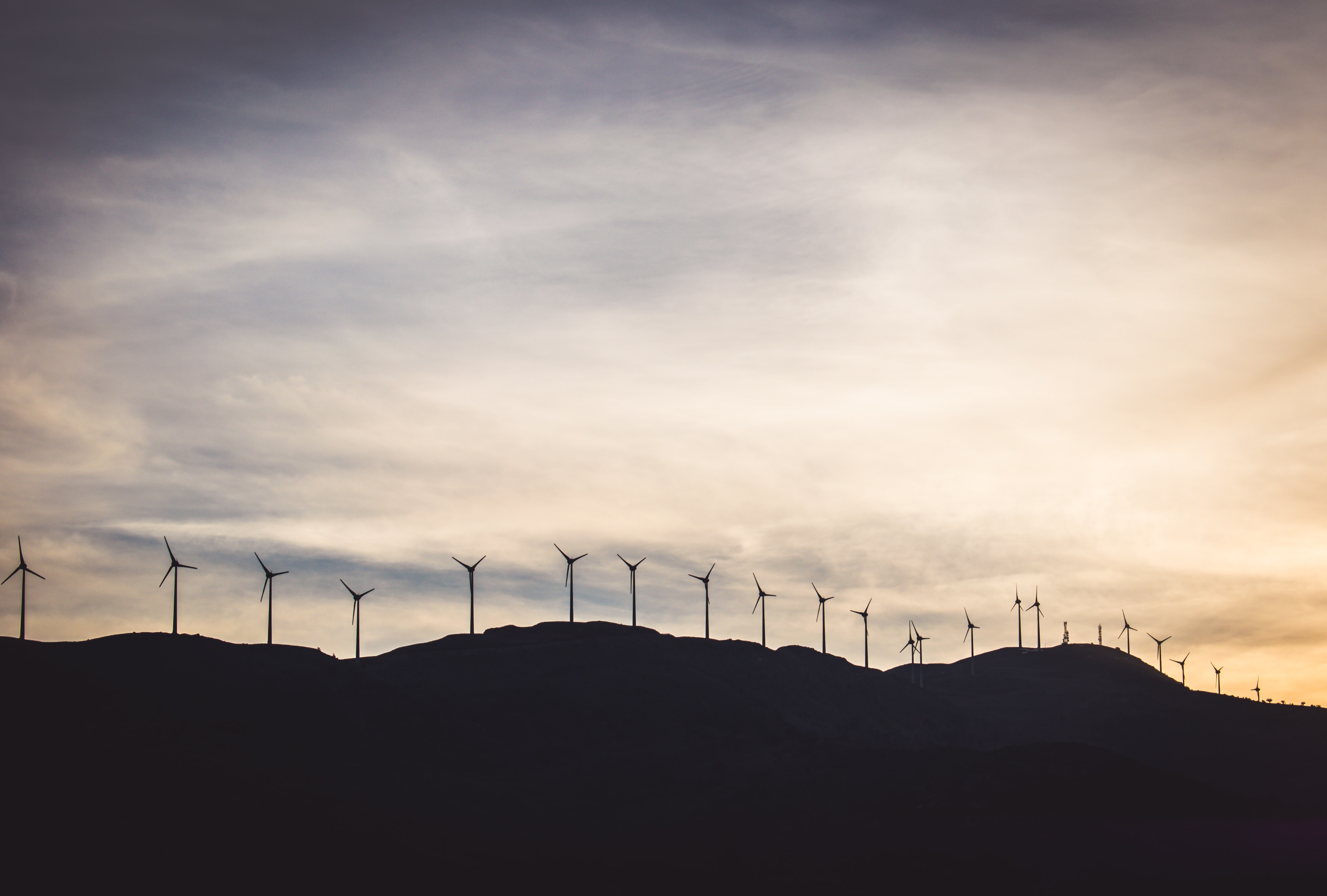 silhouette photo of wind turbines on hill