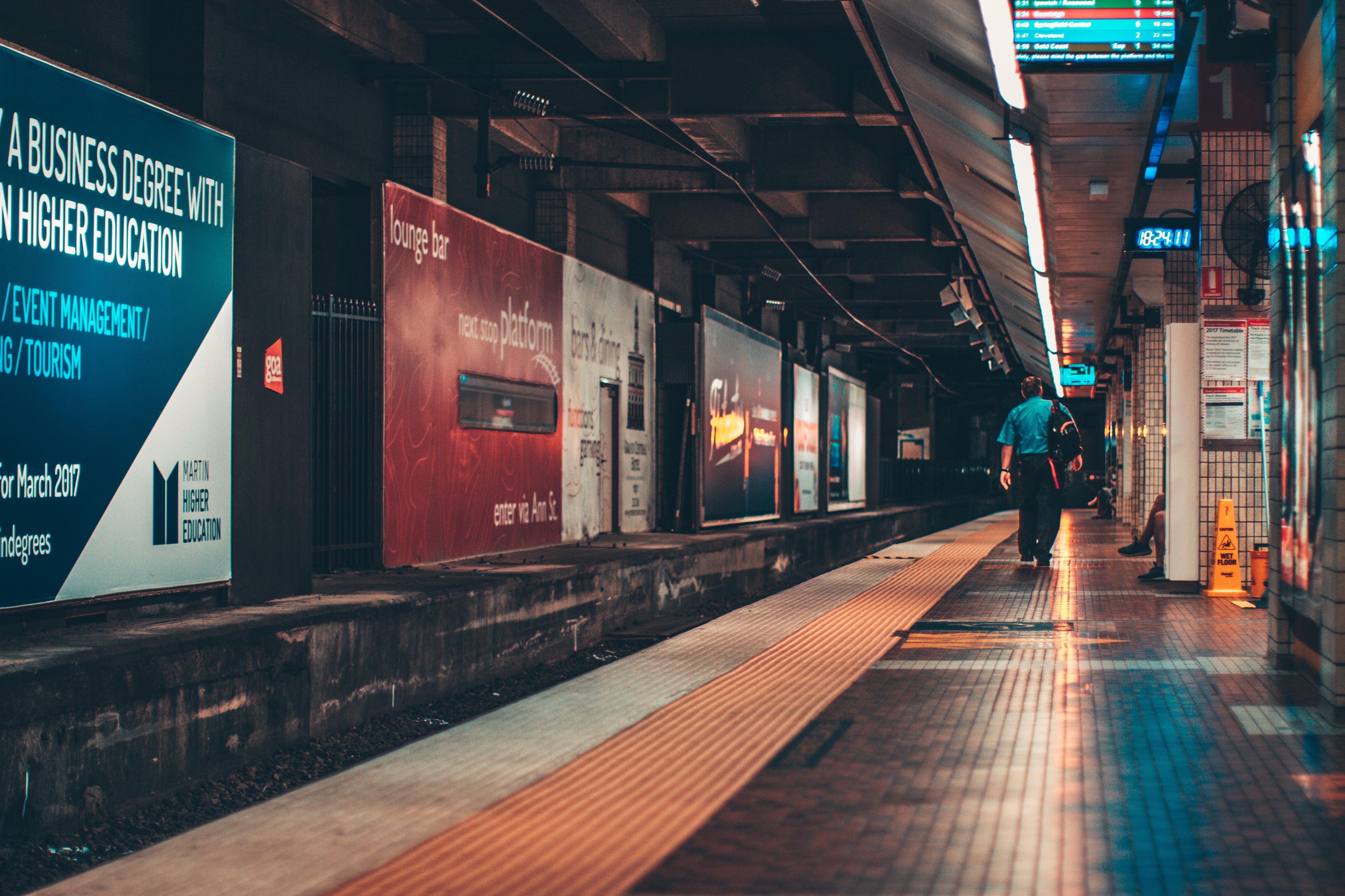 A lone man walking across the railway platform in Brisbane