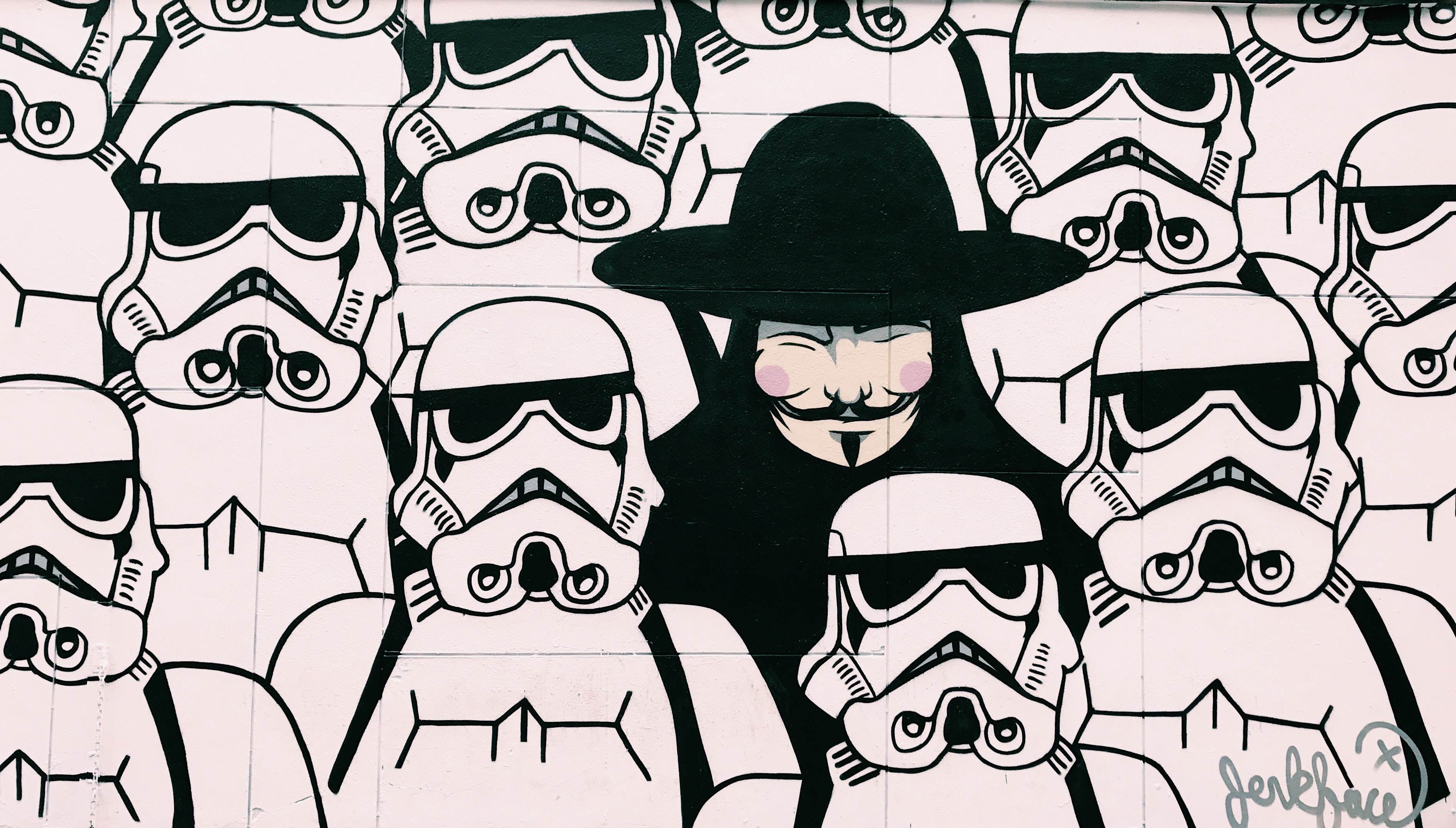 Anonymous Guy Fawkes from V from Vendetta figure amongst group of Star Wars stormtroopers in New York, Texas, United States