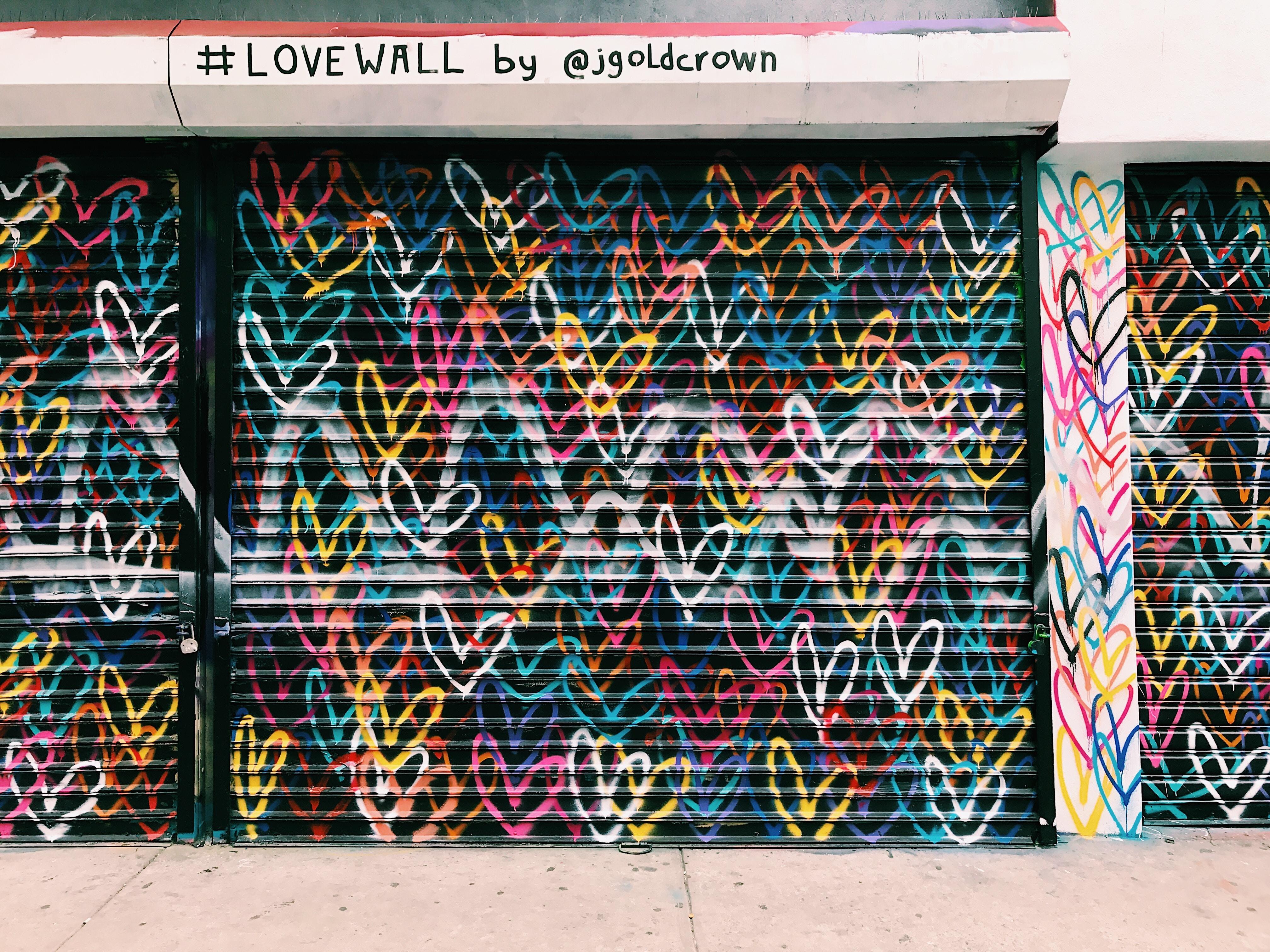 photo of black door shutter filled with heart murals