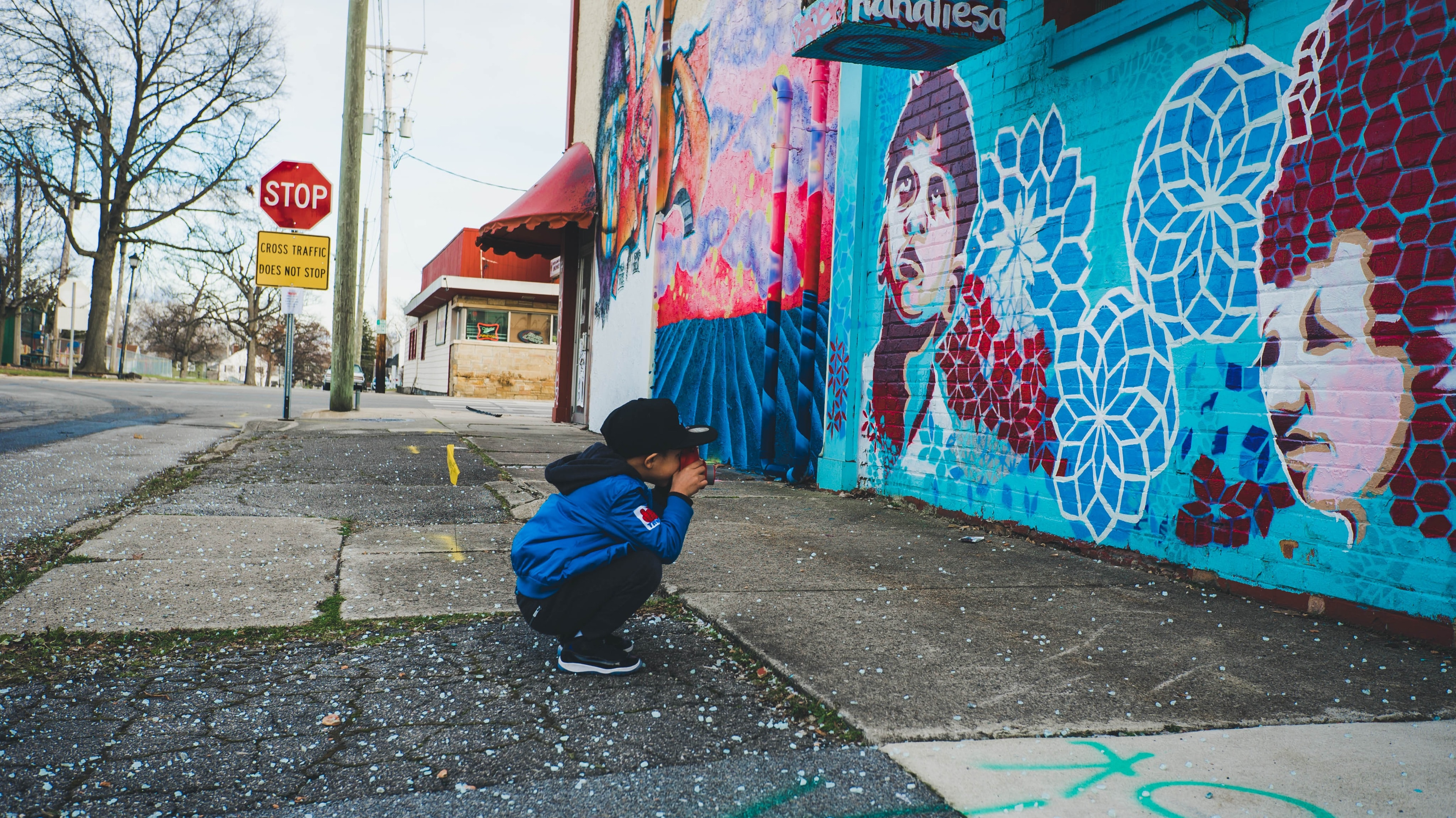 Boy taking picture of colorful street art near stop sign in New York, Texas, United States