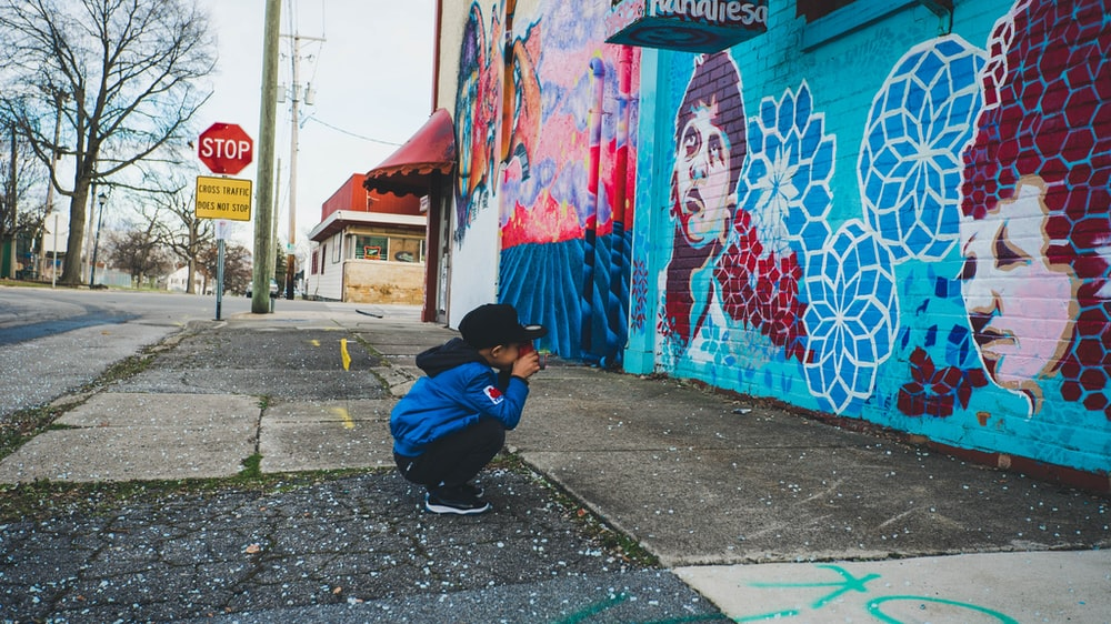 boy wearing blue hoodie in front of wall with artworks