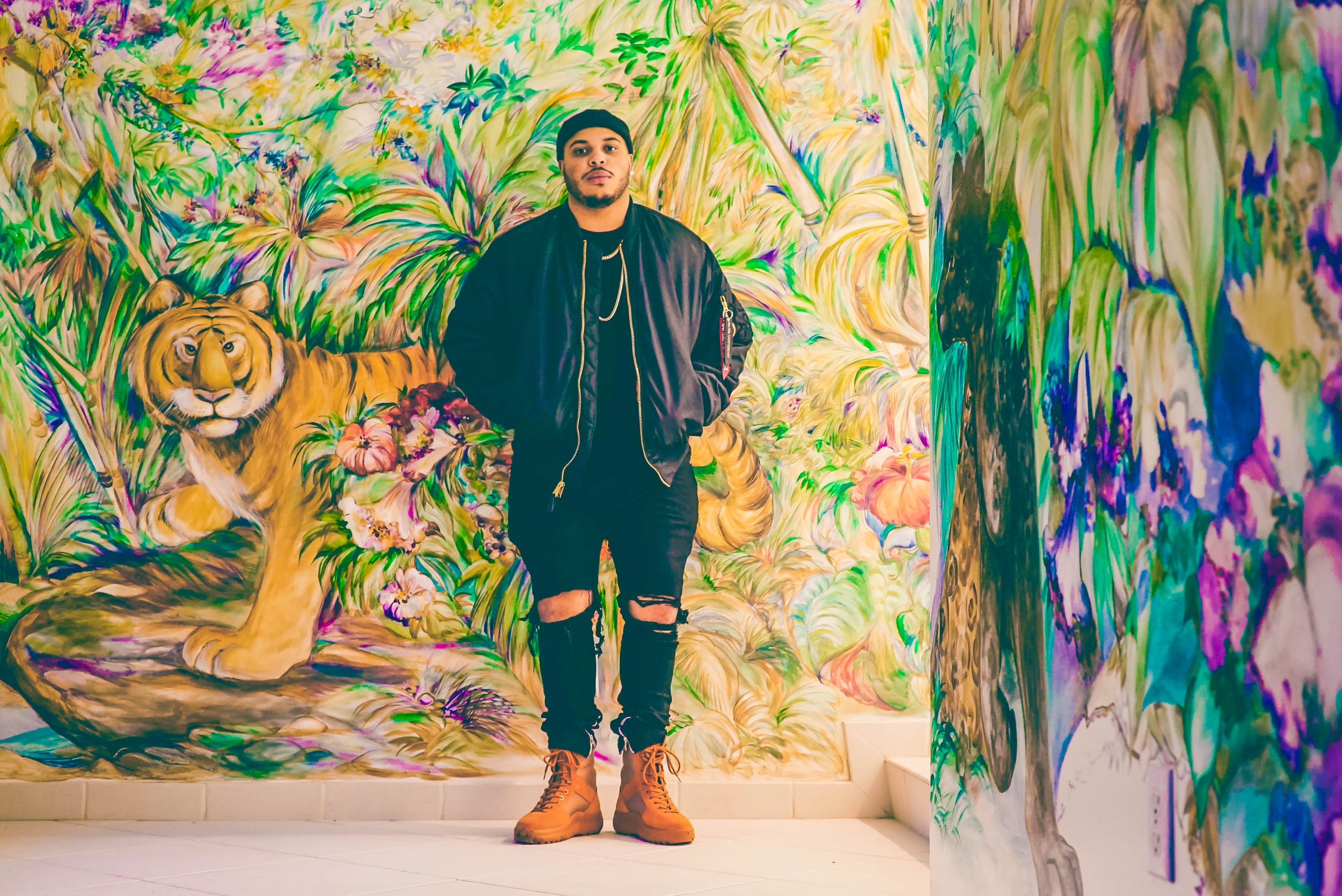 Man standing in front on a colorful mural of a tiger and jungle flowers