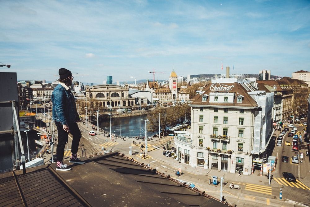 man standing on roof near buildings during daytime