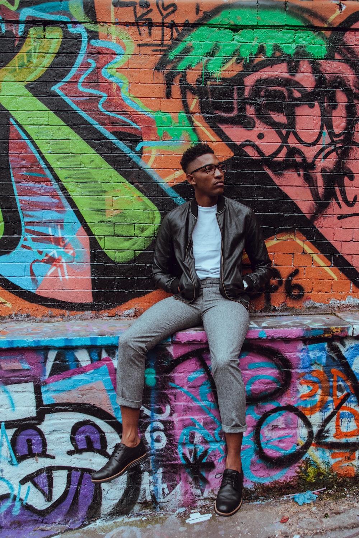 man sitting on concrete terrace with graffiti art