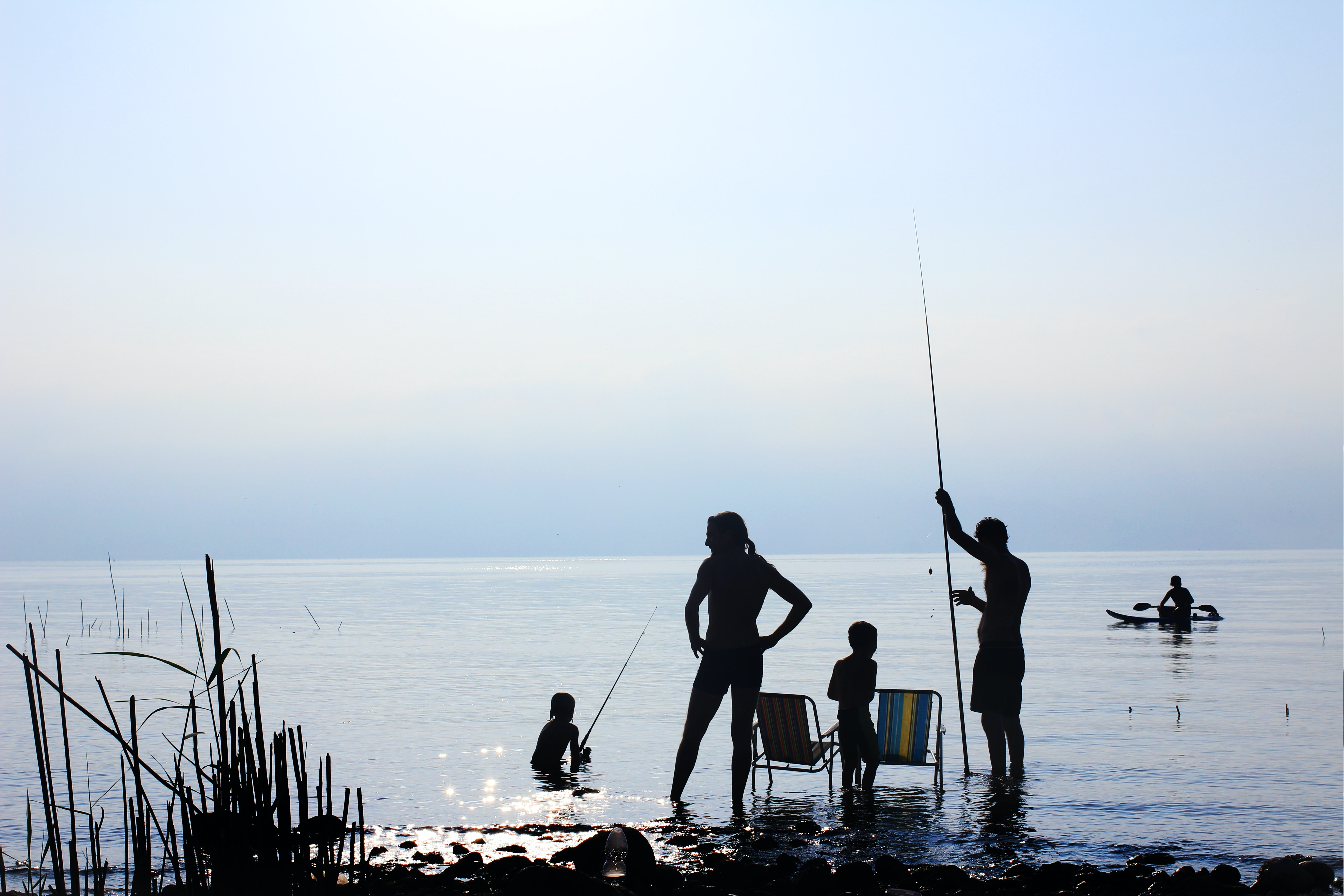Silhouettes of a family fishing by the Sea of Galilee and a man paddling in kayak