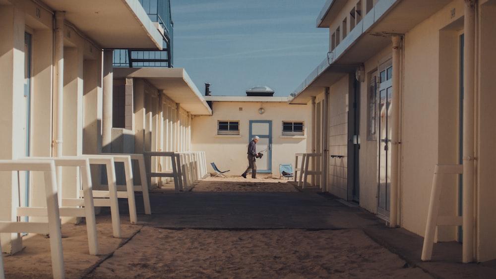 man walking between white buildings during daytime