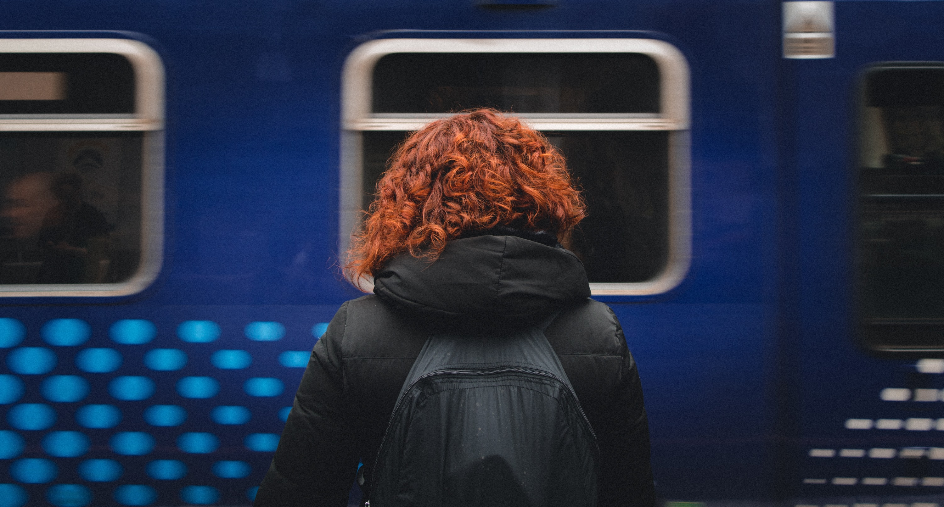 A person with curly red hair faces away toward a moving blue train in Mount Florida
