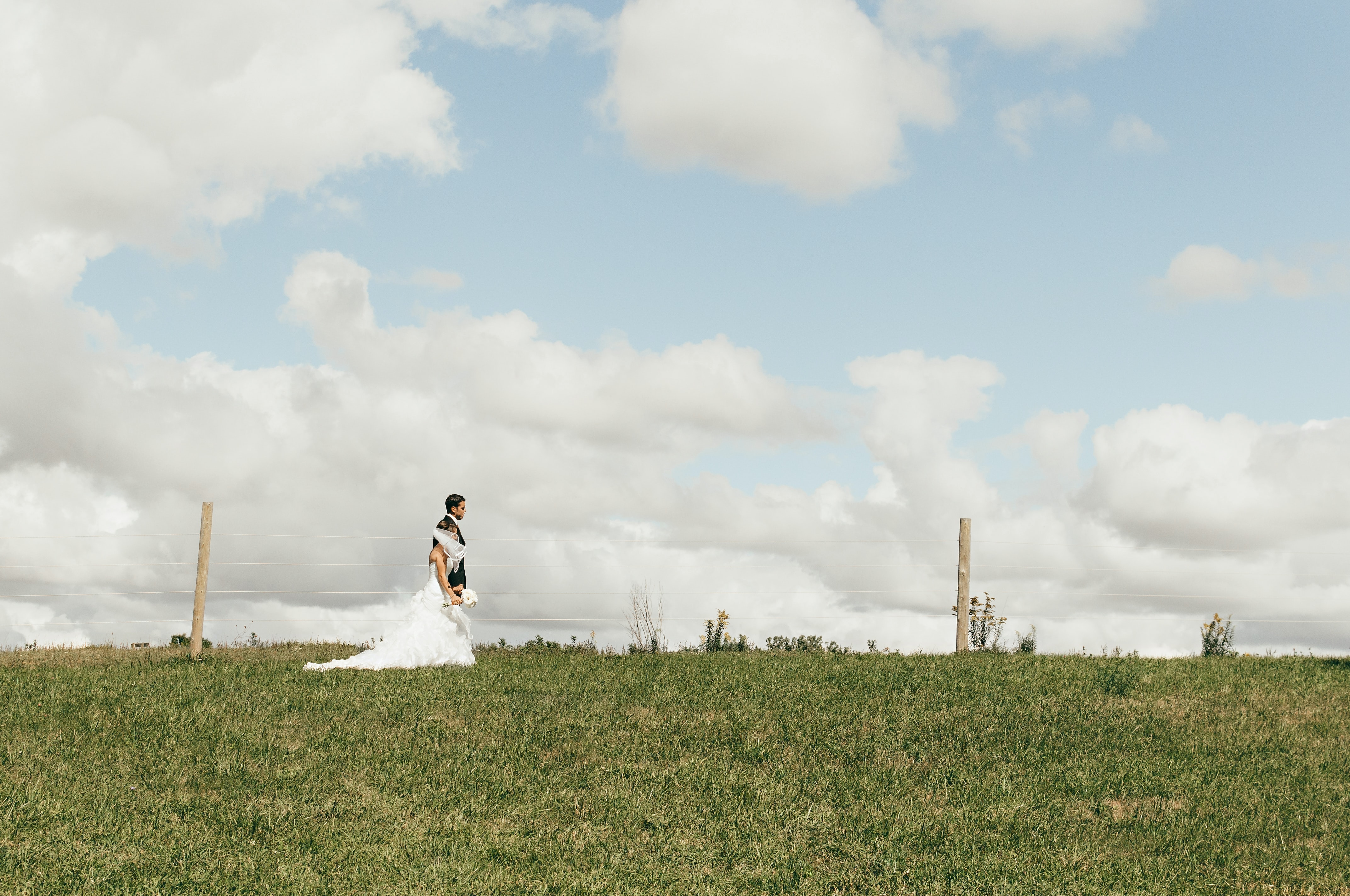 Bride and groom walking beneath the clouds in London