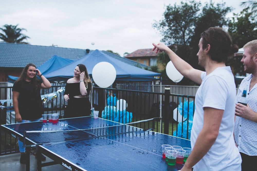 woman versus man playing beer pong under cloudy sky