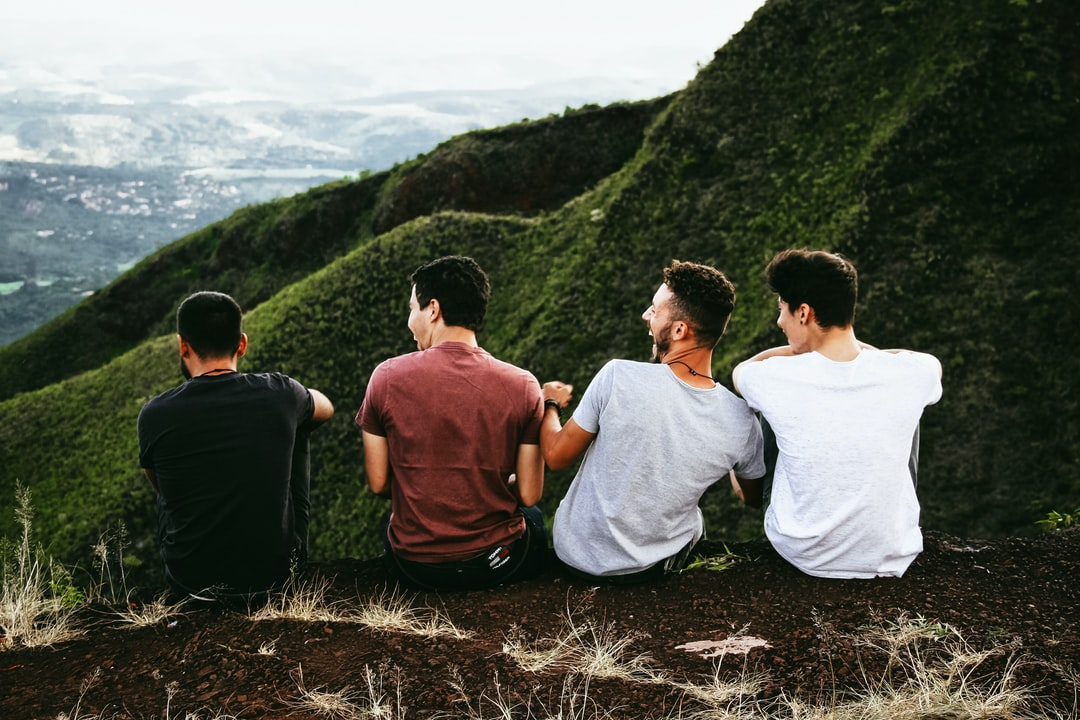 Men laughing by green valley