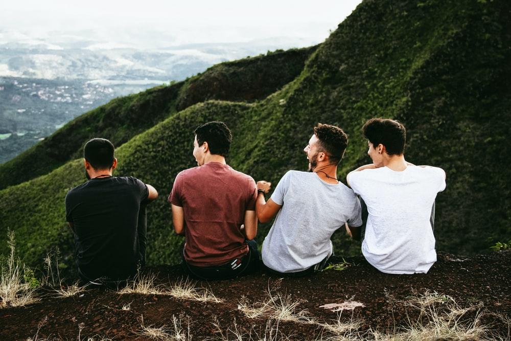 A group of four laughing men sits on an edge overlooking a green valley
