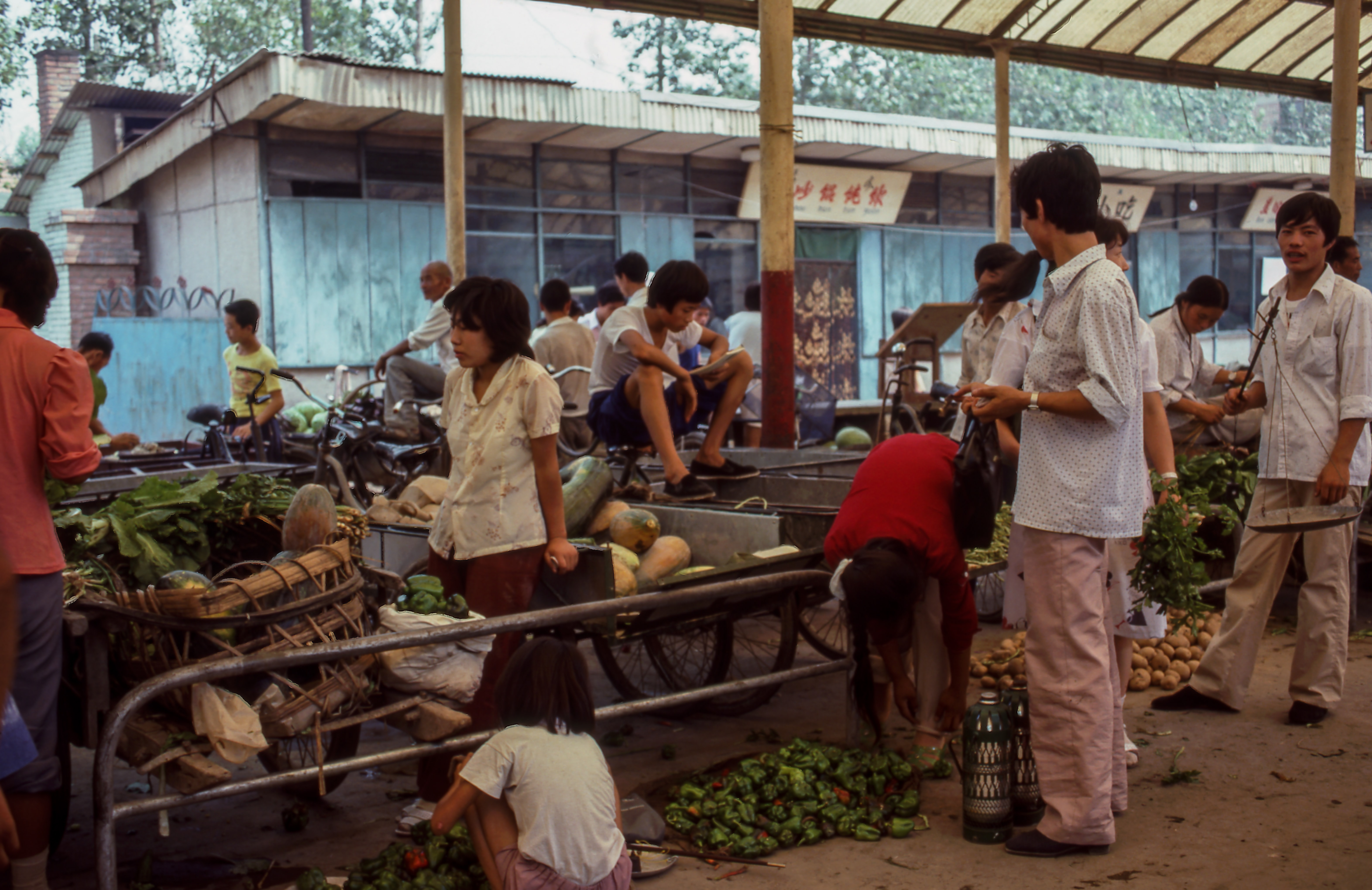 An Asian food market where many people are selling fruits and vegetables
