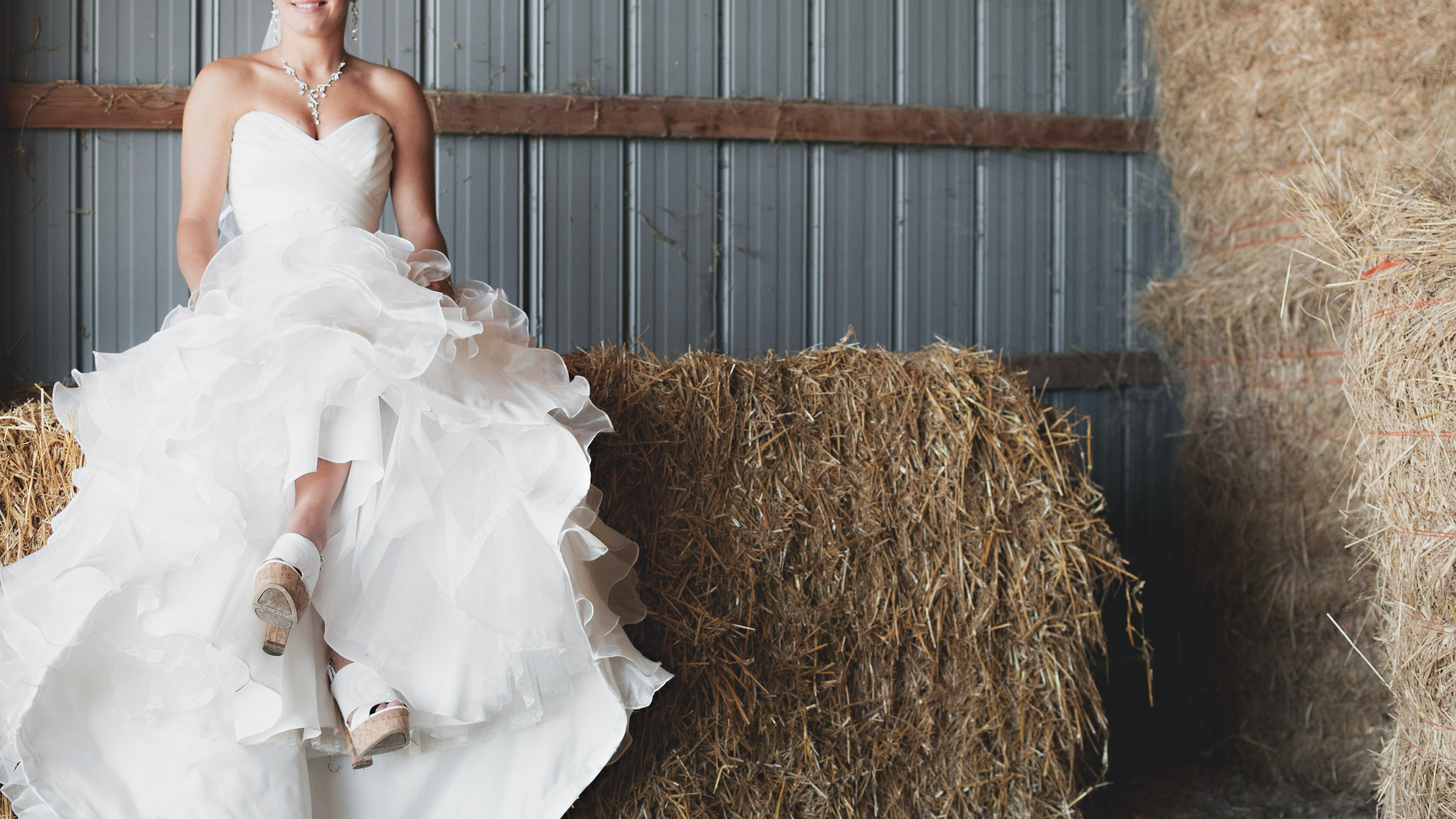 Happy bride in a wedding gown sits atop bales of hay in a barn