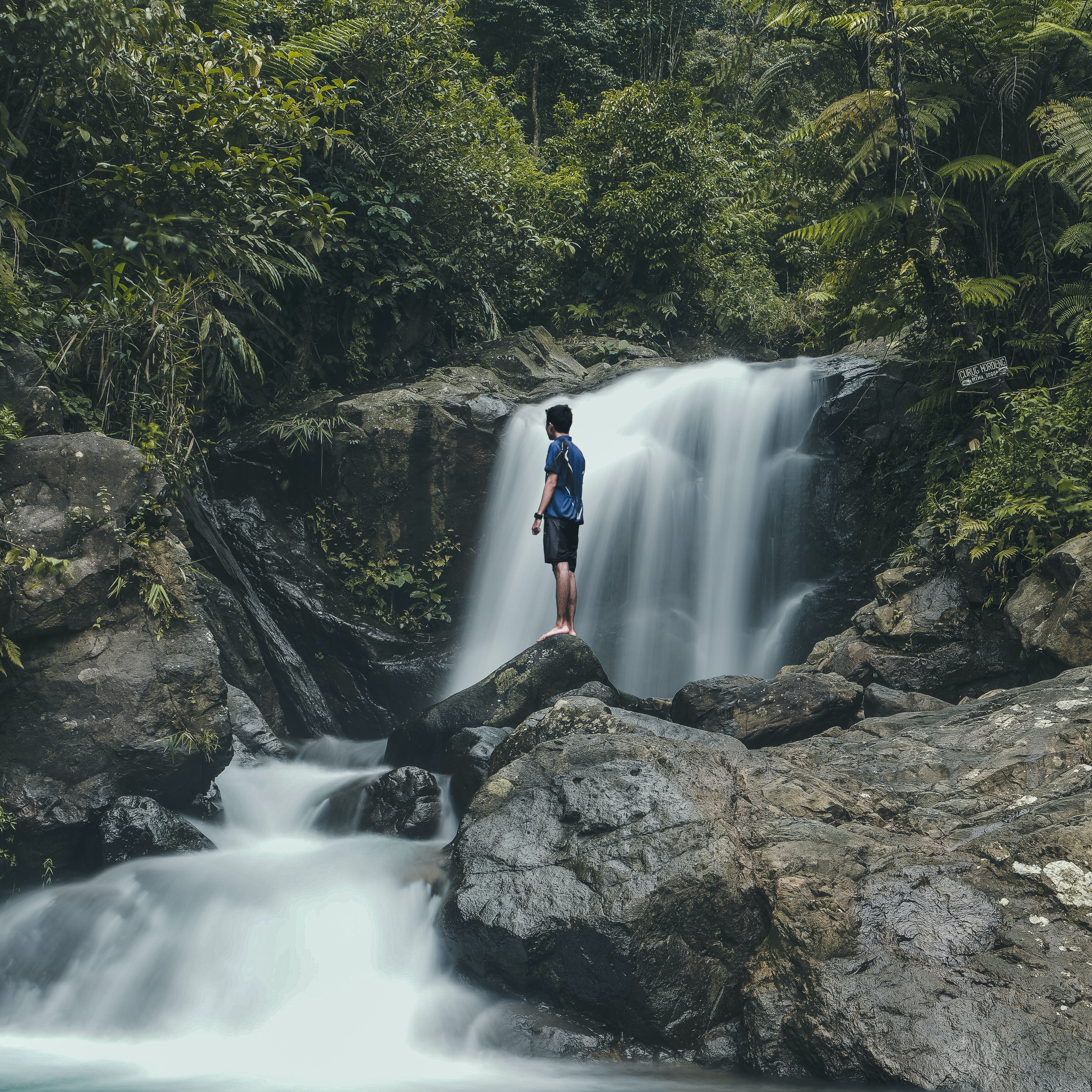man standing on rocks with waterfalls background