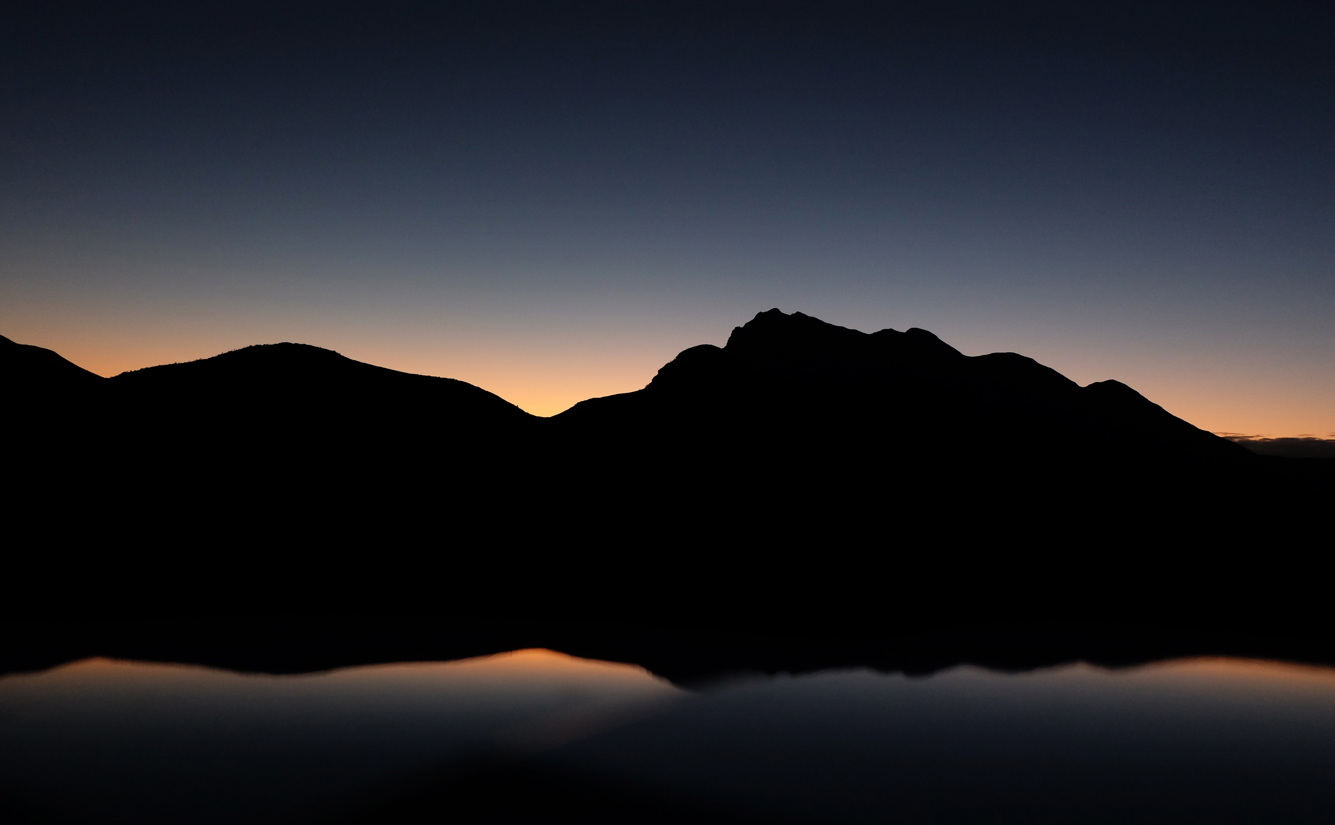 A silhouette of New York, Texas mountains during a dark sunset being reflected on still waters