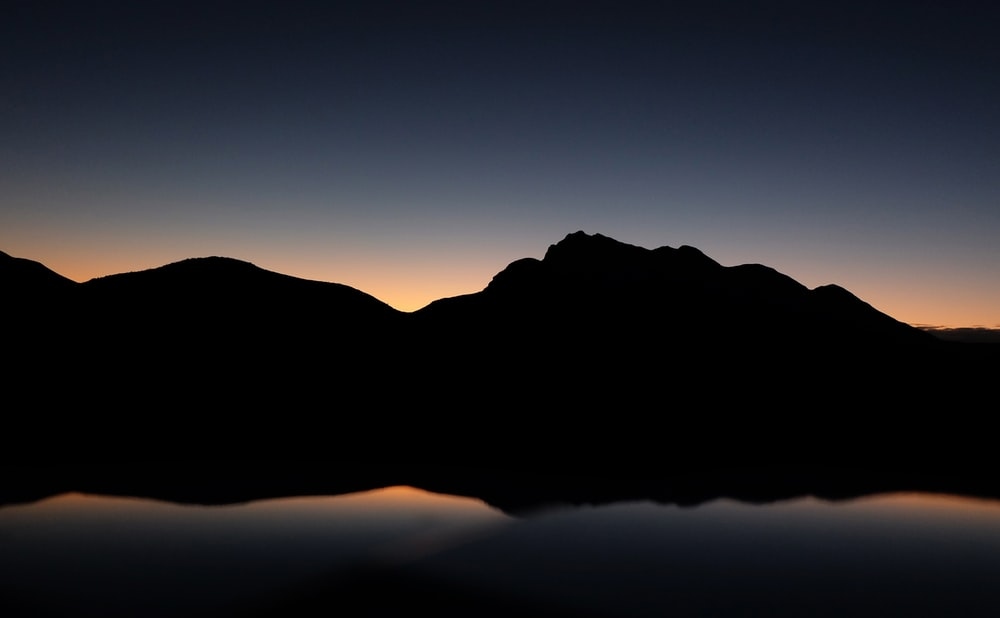 silhouette photography of mountain near body of water