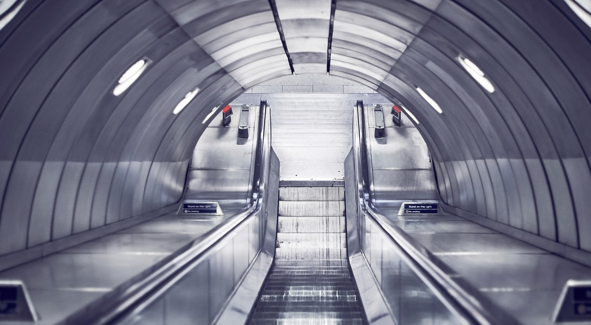 view down the escalators of a station on the london underground