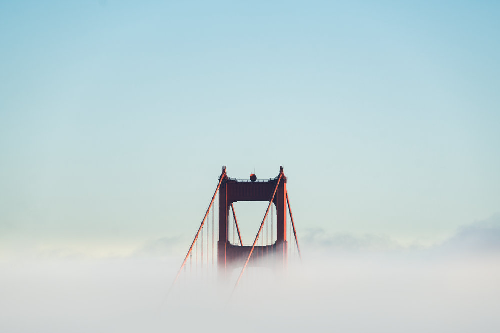 red concrete bridge surrounded by clouds