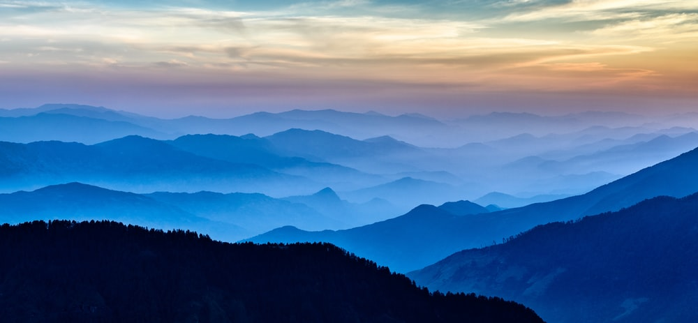 silhouette of mountains covered by fogs at the horizon