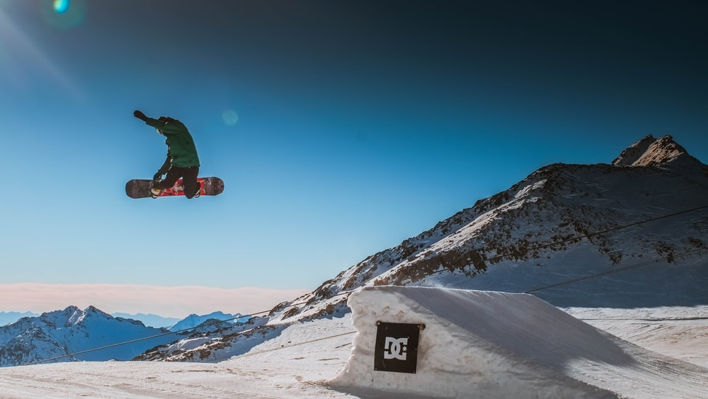 person wearing green jacket jumping on white snow ramp during daytime