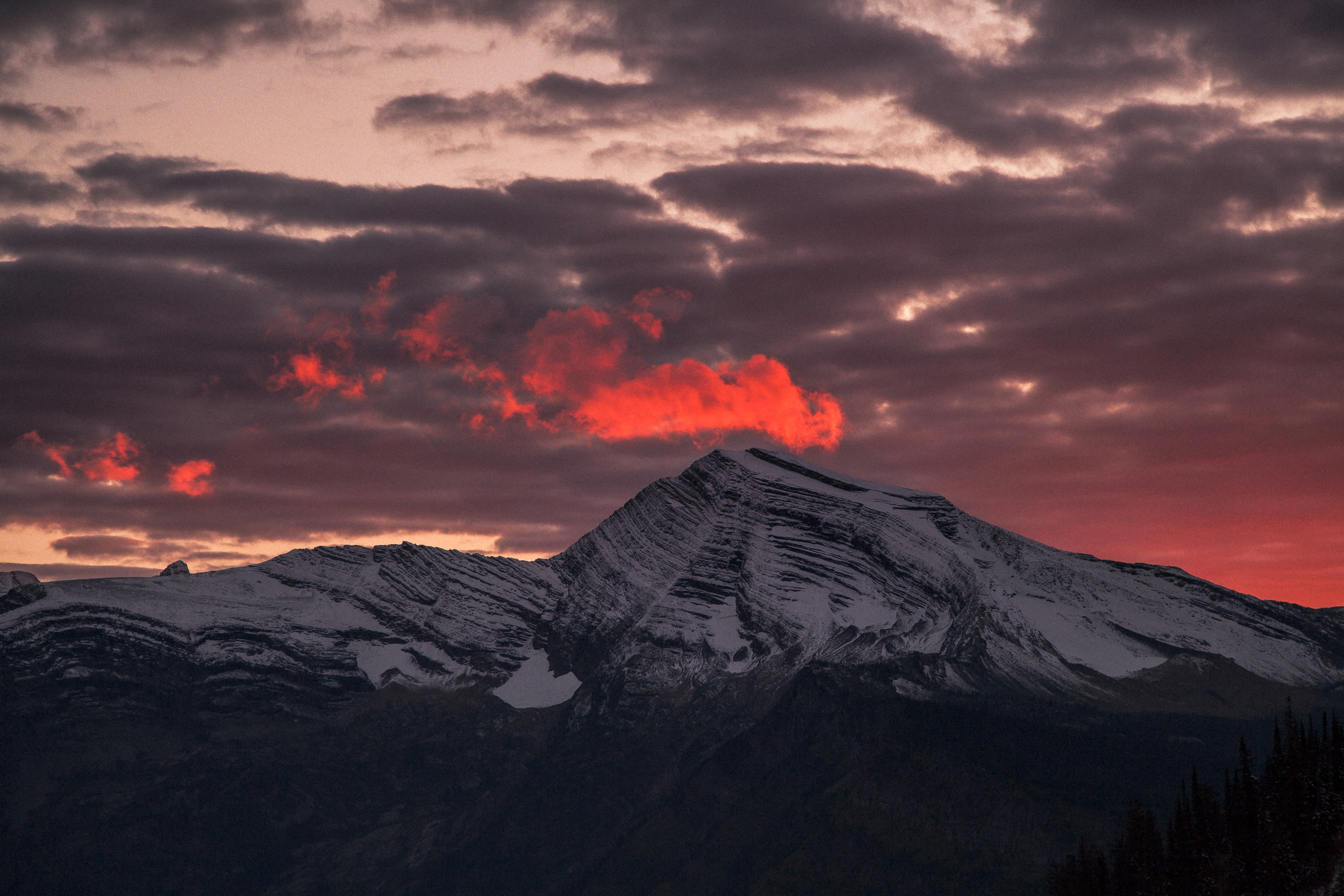 Red clouds hang over a snowy mountain ridge as sun sets over West Glacier