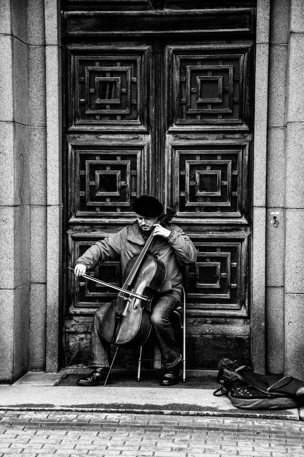 Black and white shot of street musician performing with cello in doorway in Riga