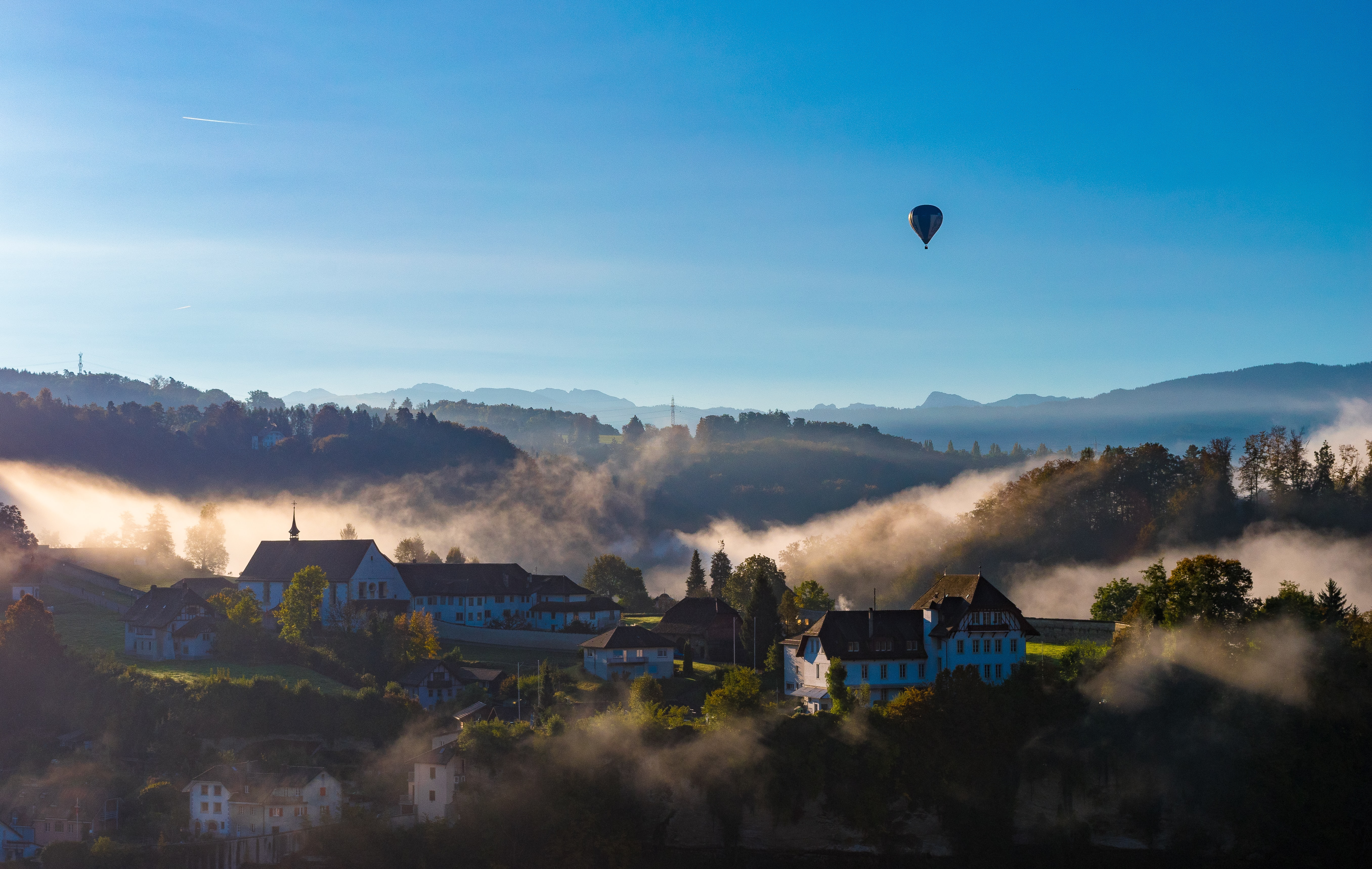 Hot air balloon flies over a quaint village in Fribourg on a foggy day