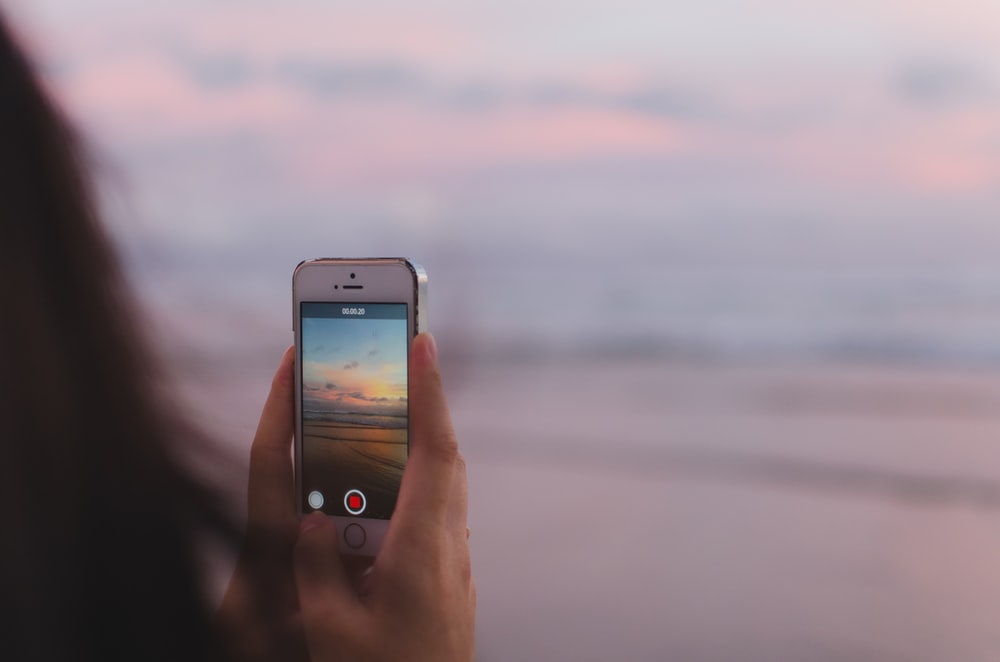 person taking a photo of of open sea and sunset