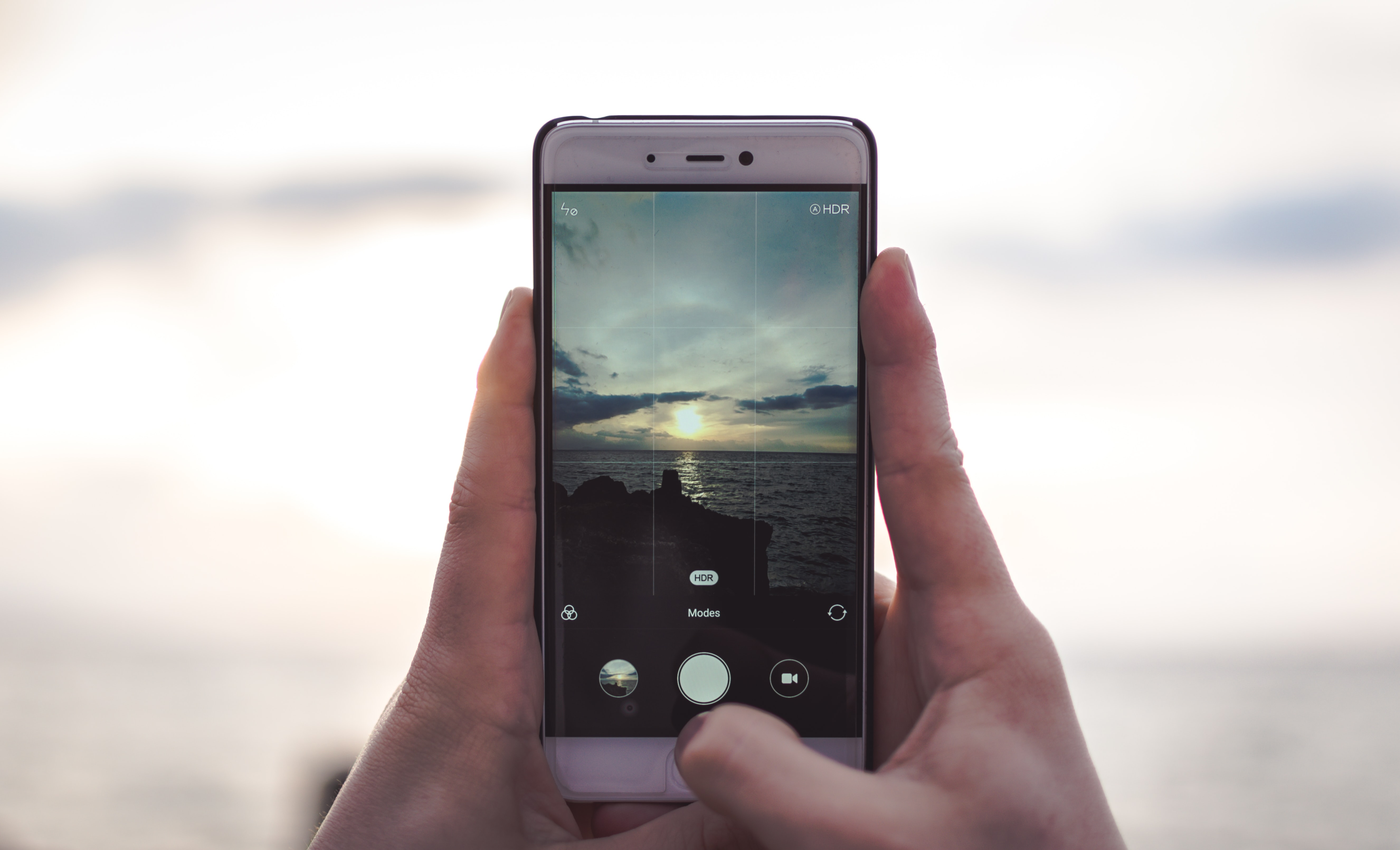 A person taking a picture of the ocean under clouds.