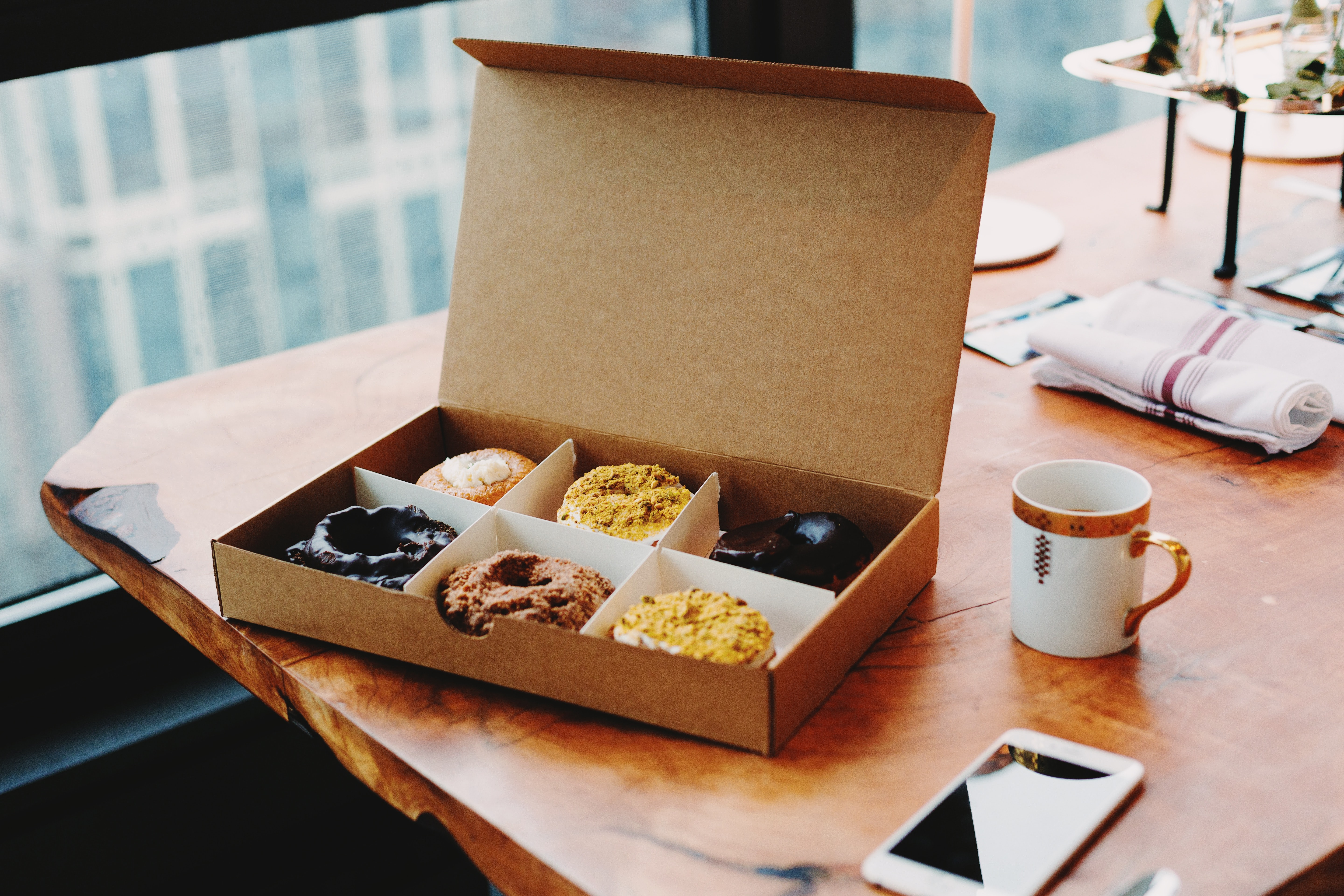 Various donuts in a cardboard box on a table